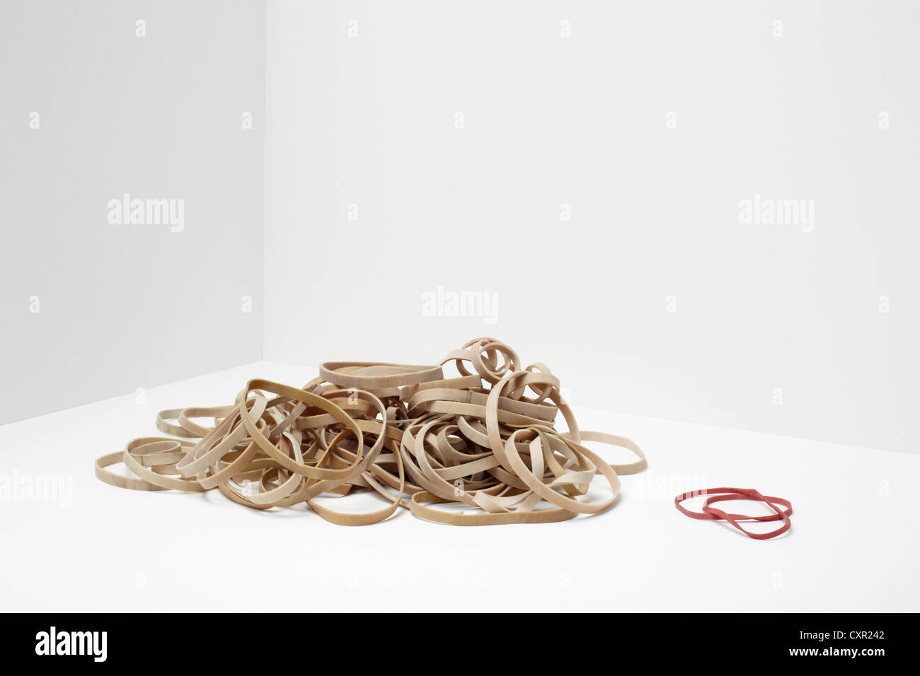 Stack of rubber bands with two red rubber bands - Stock Image