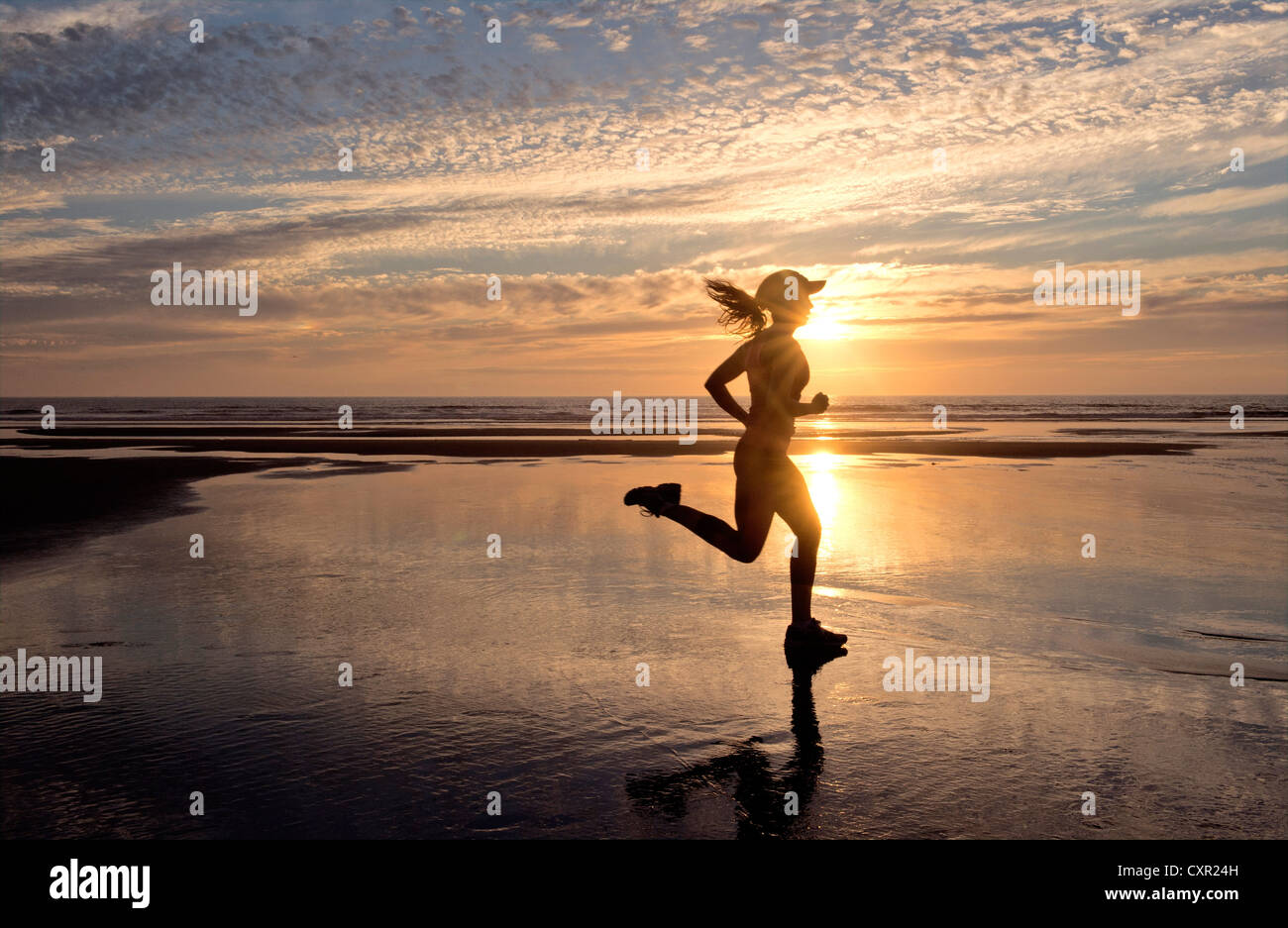 Woman running on beach at sunrise - Stock Image