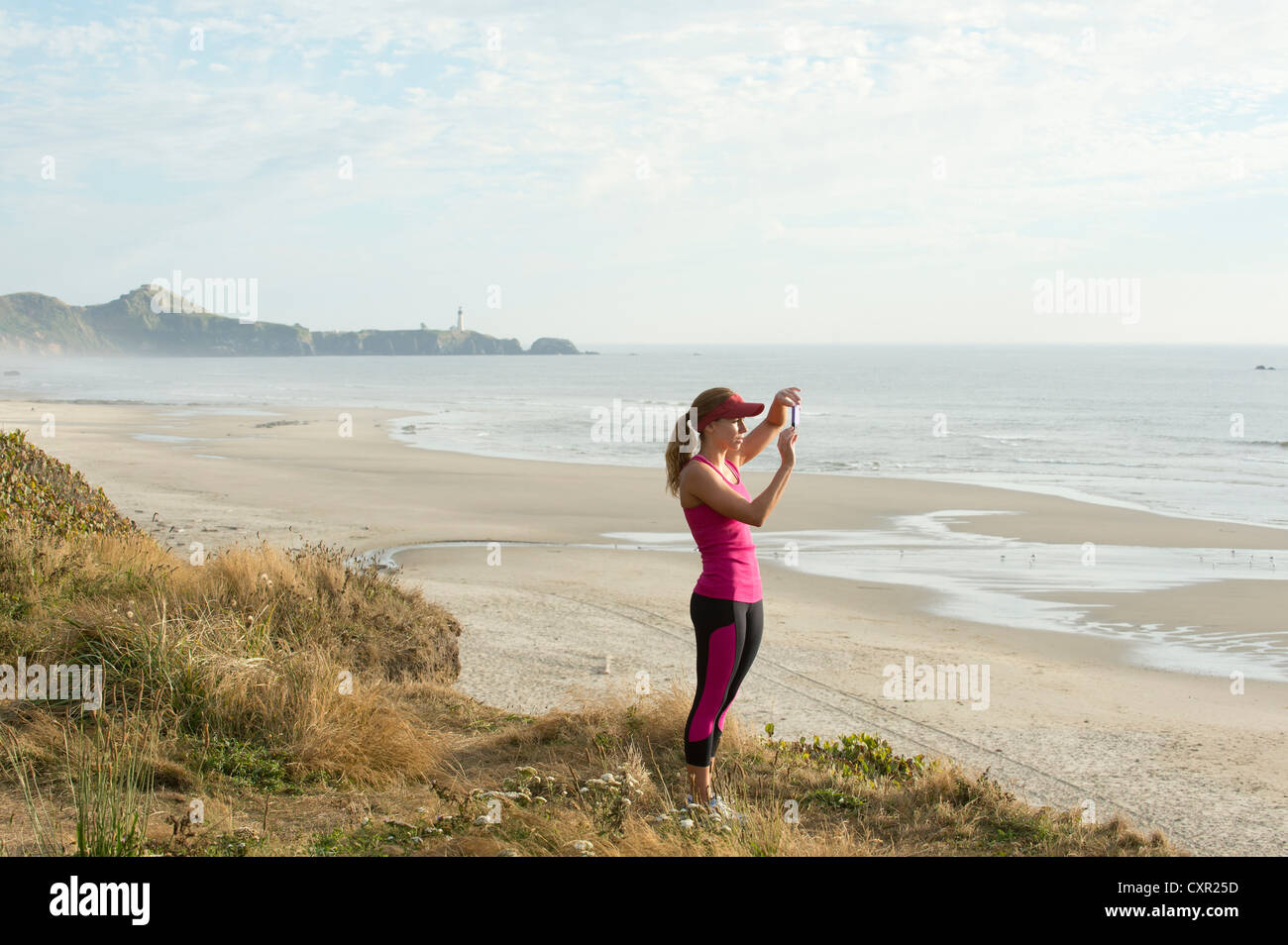 Active young woman taking photograph at the beach - Stock Image