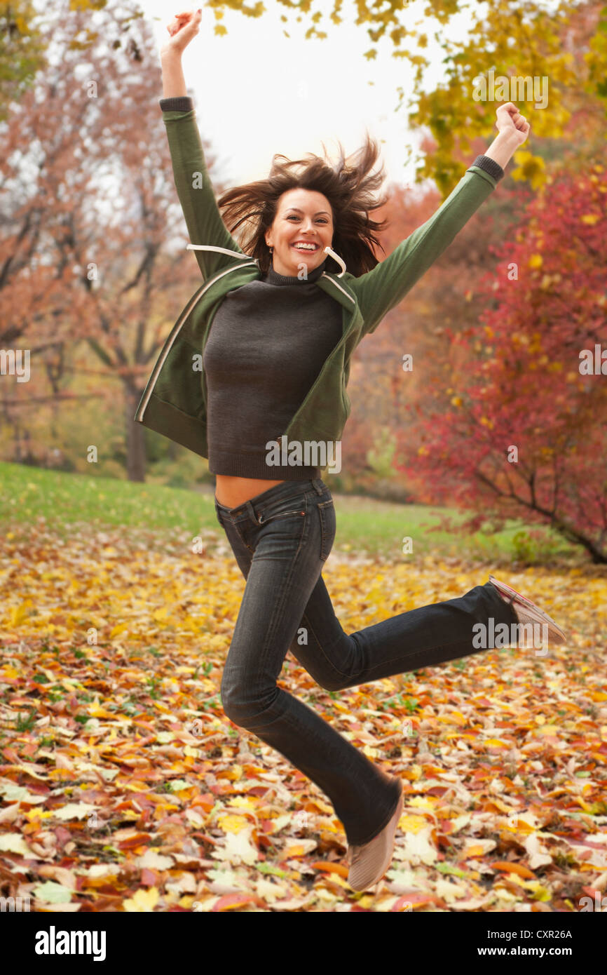 Woman jumping in autumn leaves - Stock Image