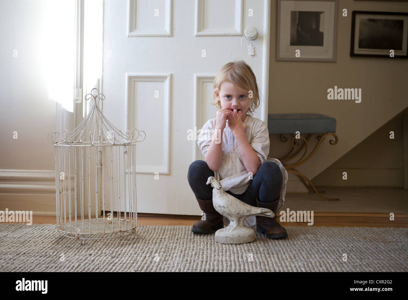 Little girl by door with birdcage and bird statue - Stock Image