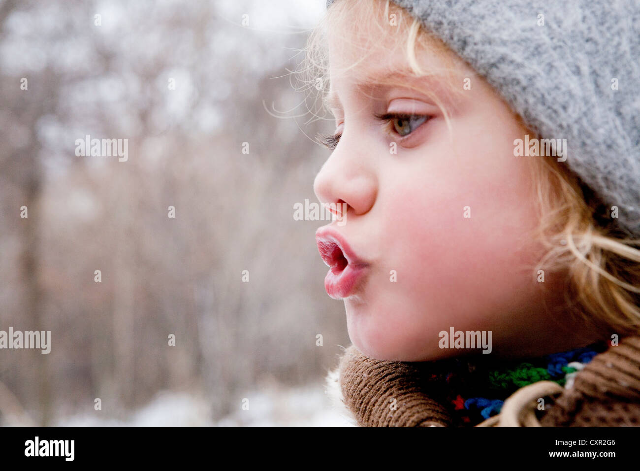 Little girl looking at her breath in the cold air - Stock Image