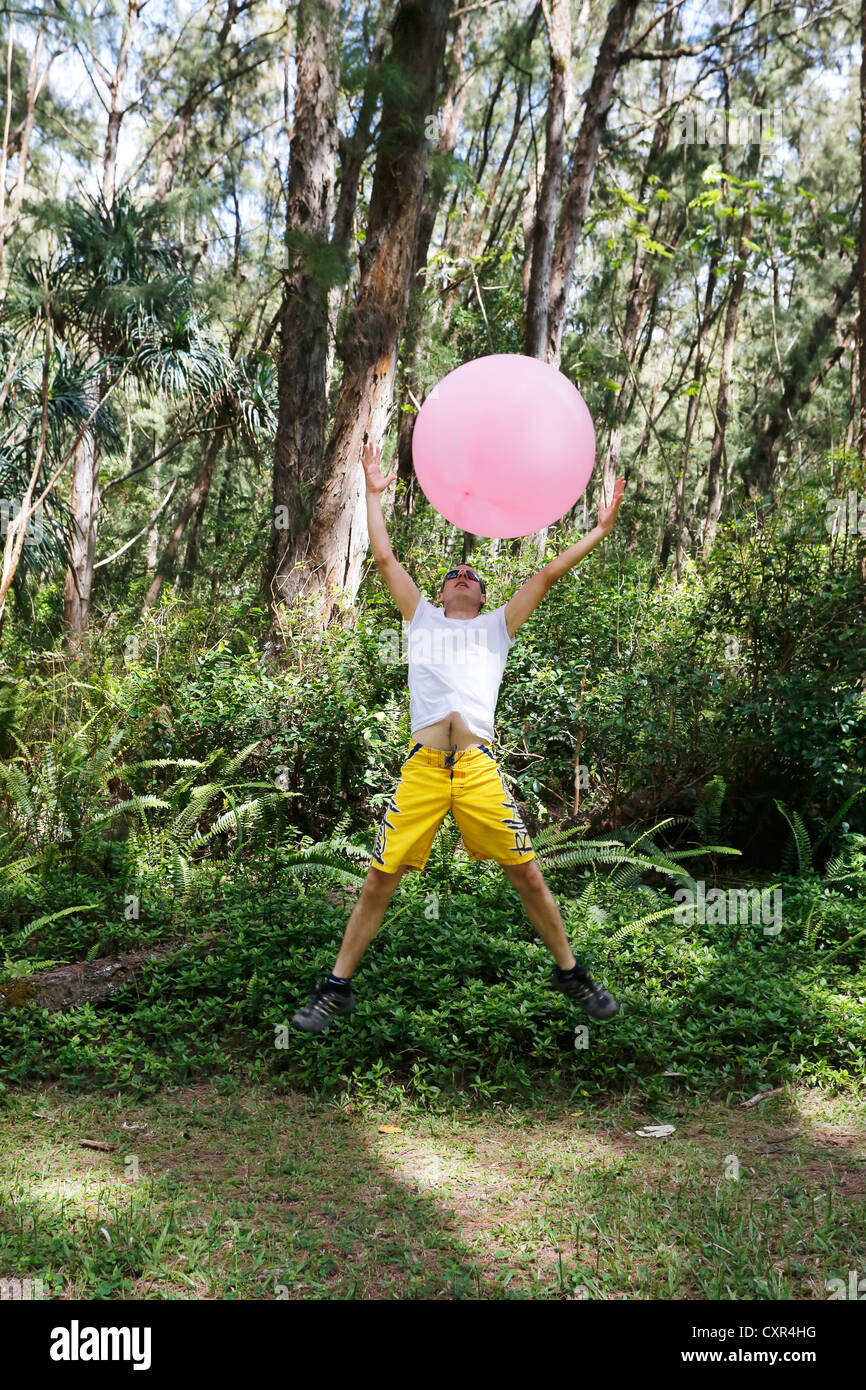 Man with a balloon in the woods, lightness and freedom, Nanawale Hills, Big Island, Hawaii, USA - Stock Image