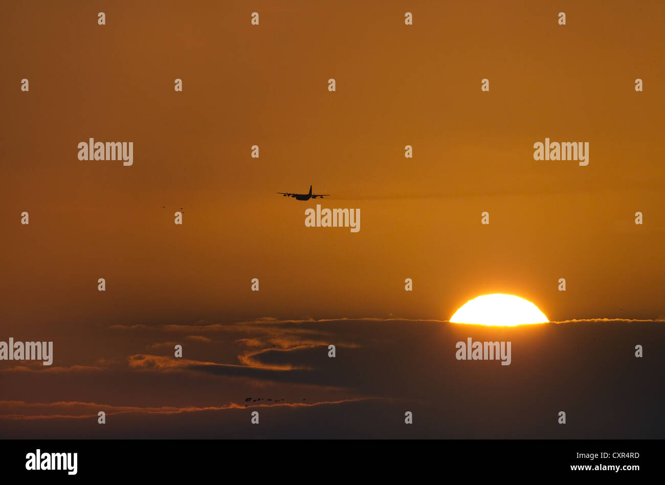 RAF Airplane at sunset over tidal creeks Norfolk - Stock Image