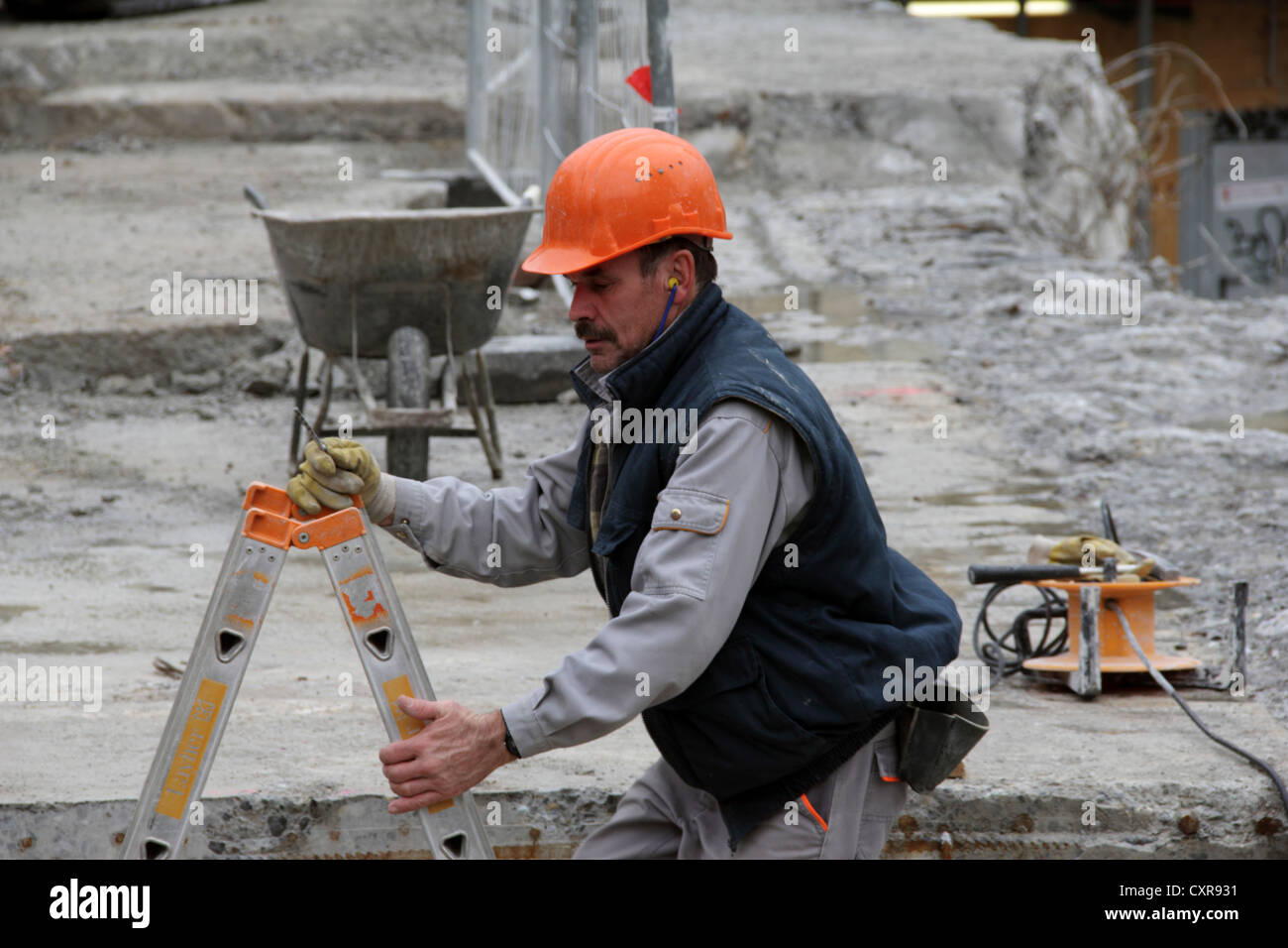 Construction worker climbing onto a concrete slab to work there - Stock Image