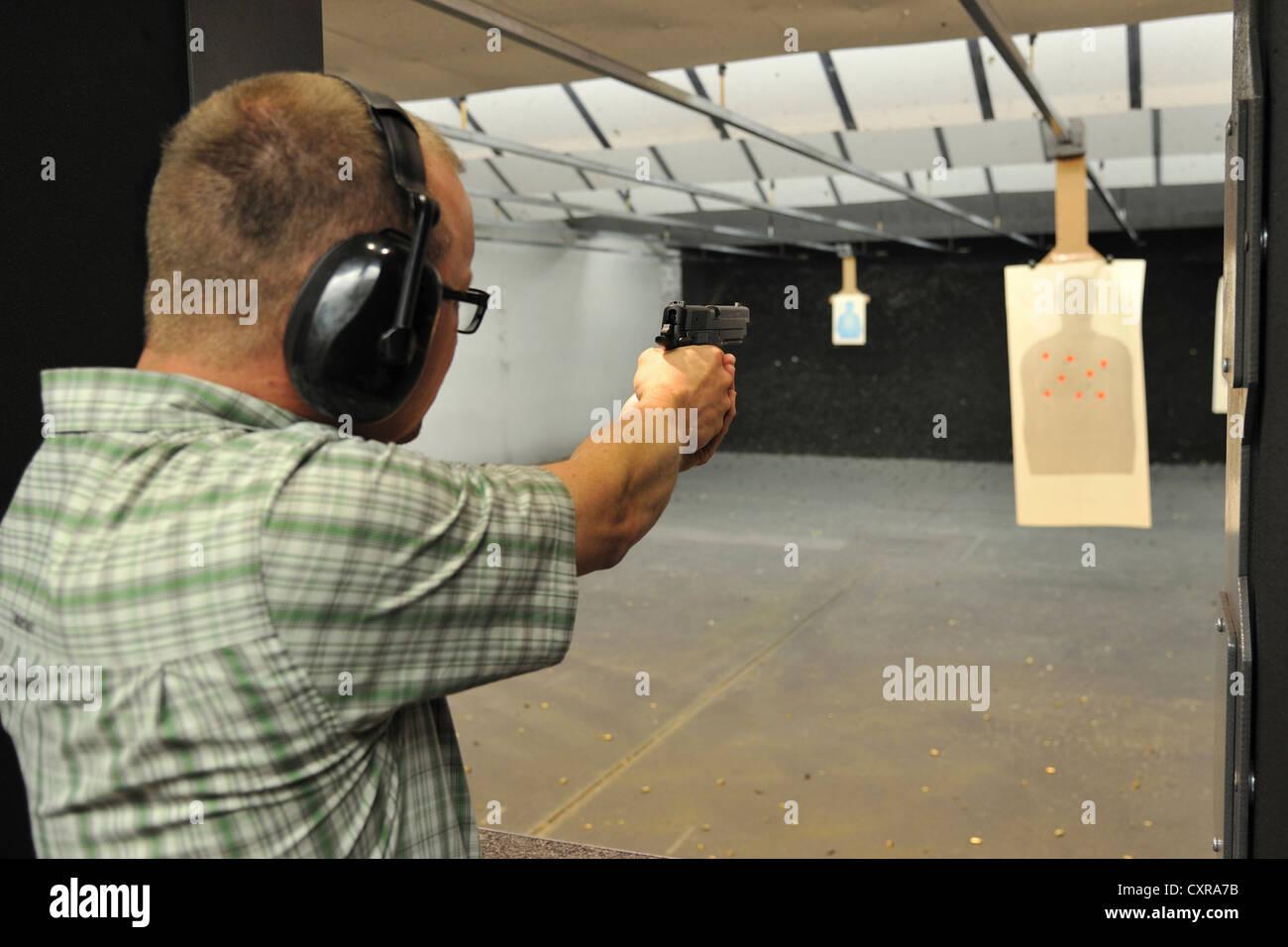 Male shooter aiming handgun during targeting practice at firing range, Colorado, USA - Stock Image