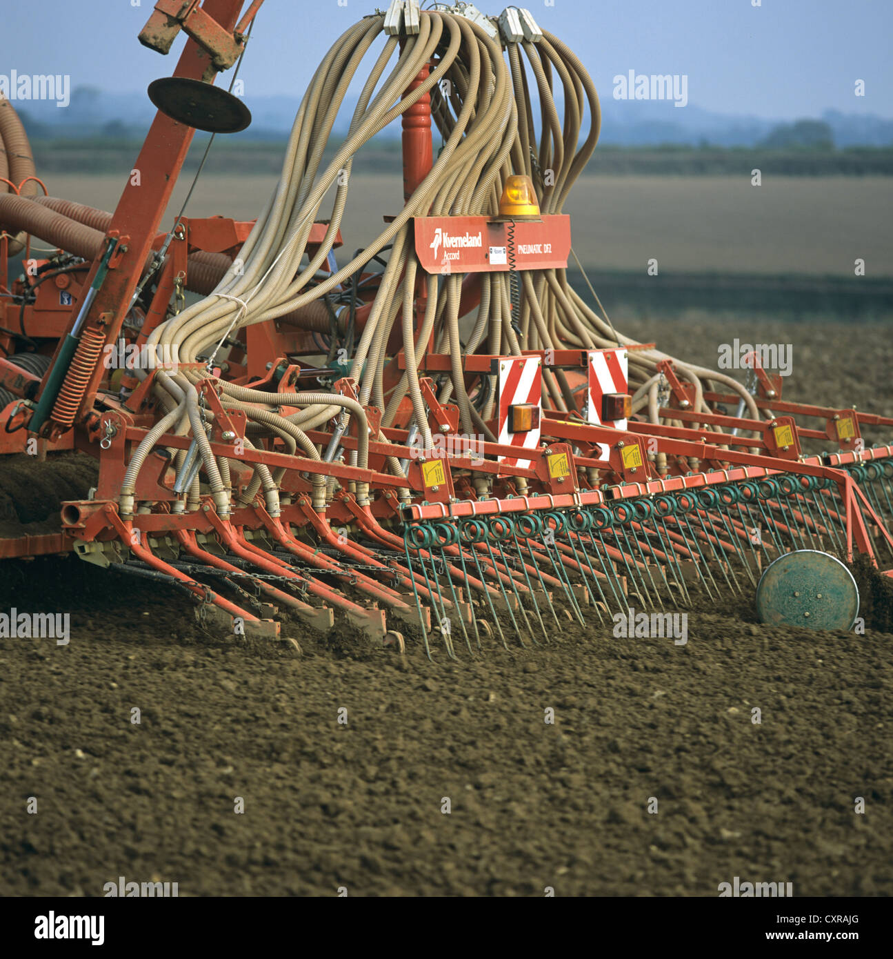 Planting cereal crop with a Kvernland pneumatic drill mounted on John Deere tractor, Devon - Stock Image