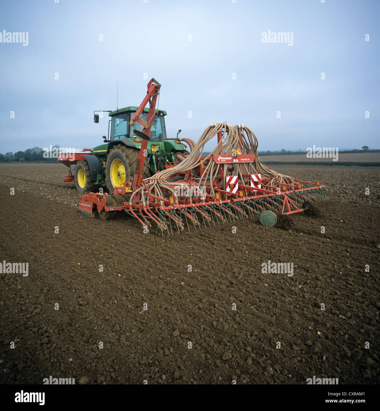 John Deere tractor and pneumatic drill planting a cereal crop - Stock Image