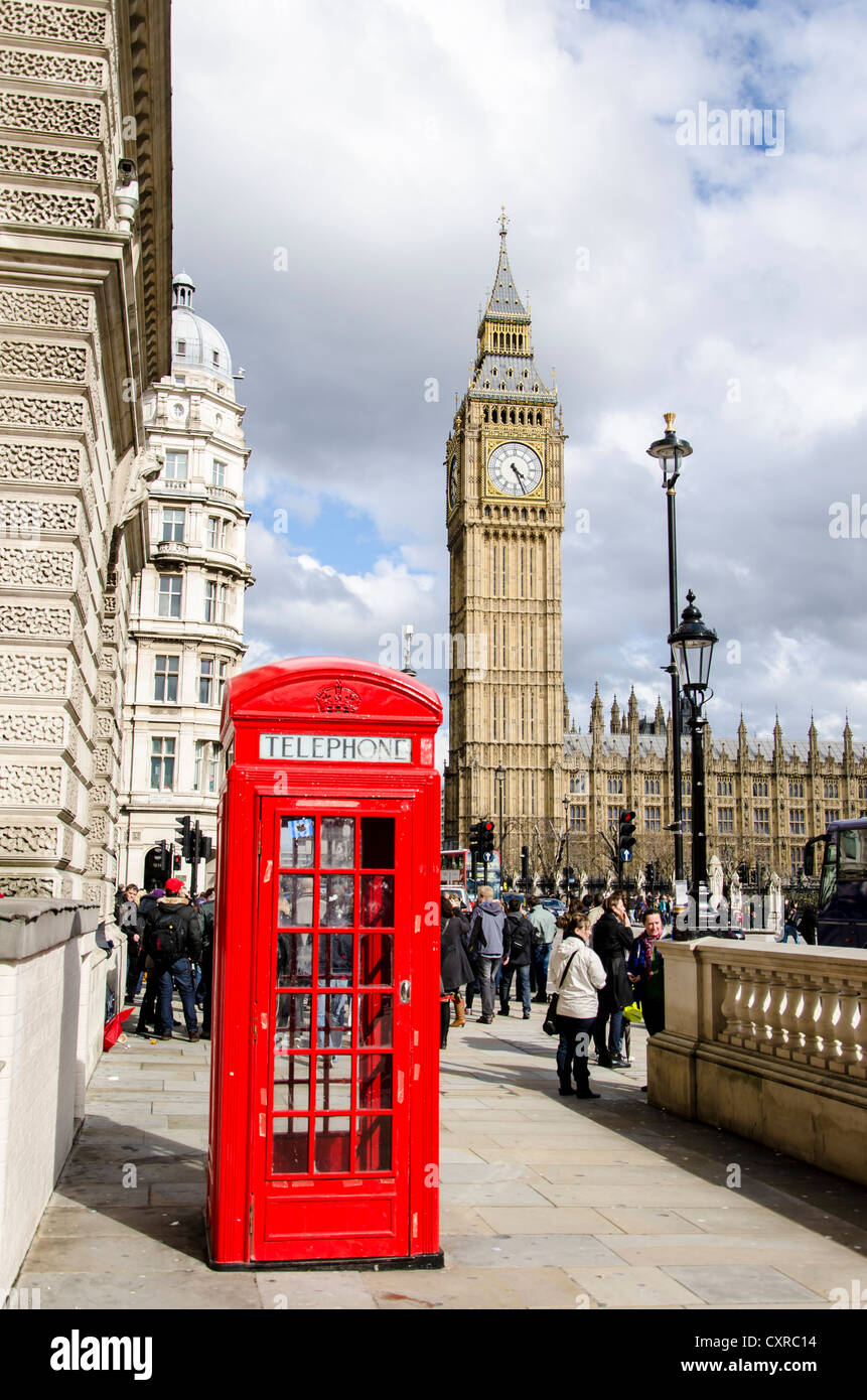 Red telephone booth in front of the clock or bell tower, Big Ben, of the Houses or Parliament, London, South England, Stock Photo
