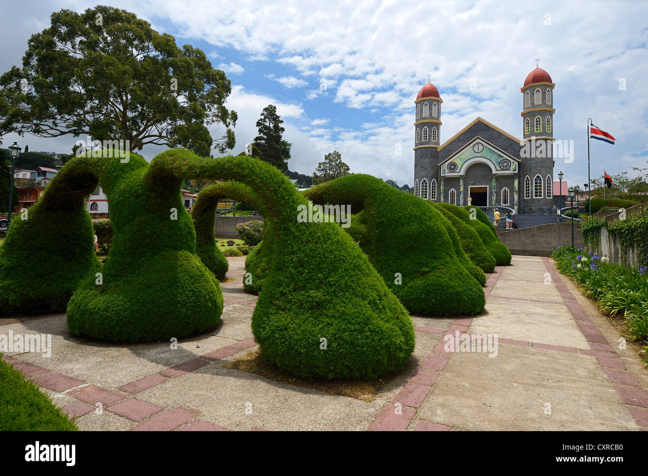 Landscaped park designed by Evangelista Blanco with artfully trimmed cypress trees, church San Rafael at back, Zarcero - Stock Image