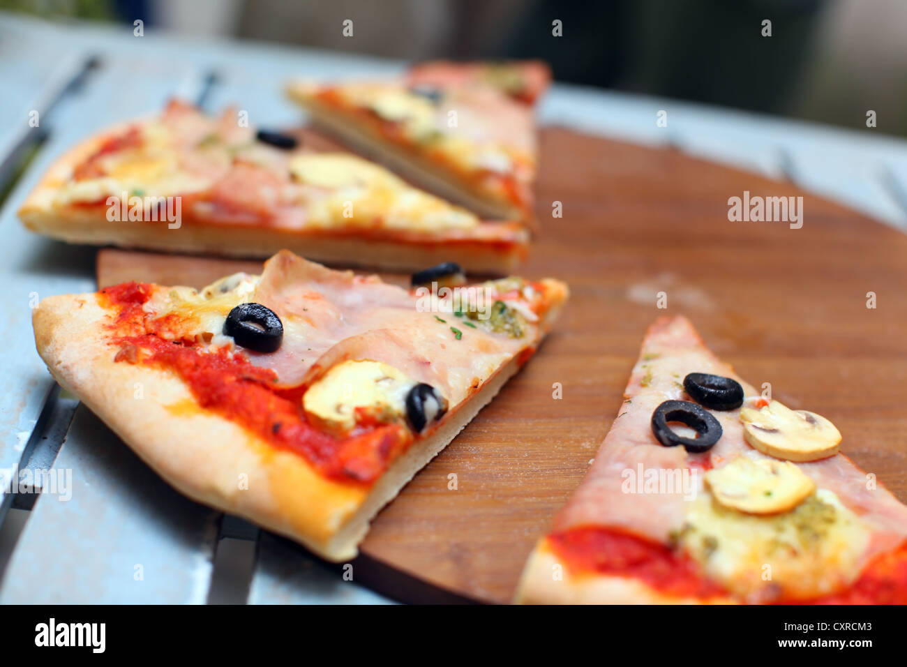 Sliced pizza with ham and olives on a wooden board - Stock Image