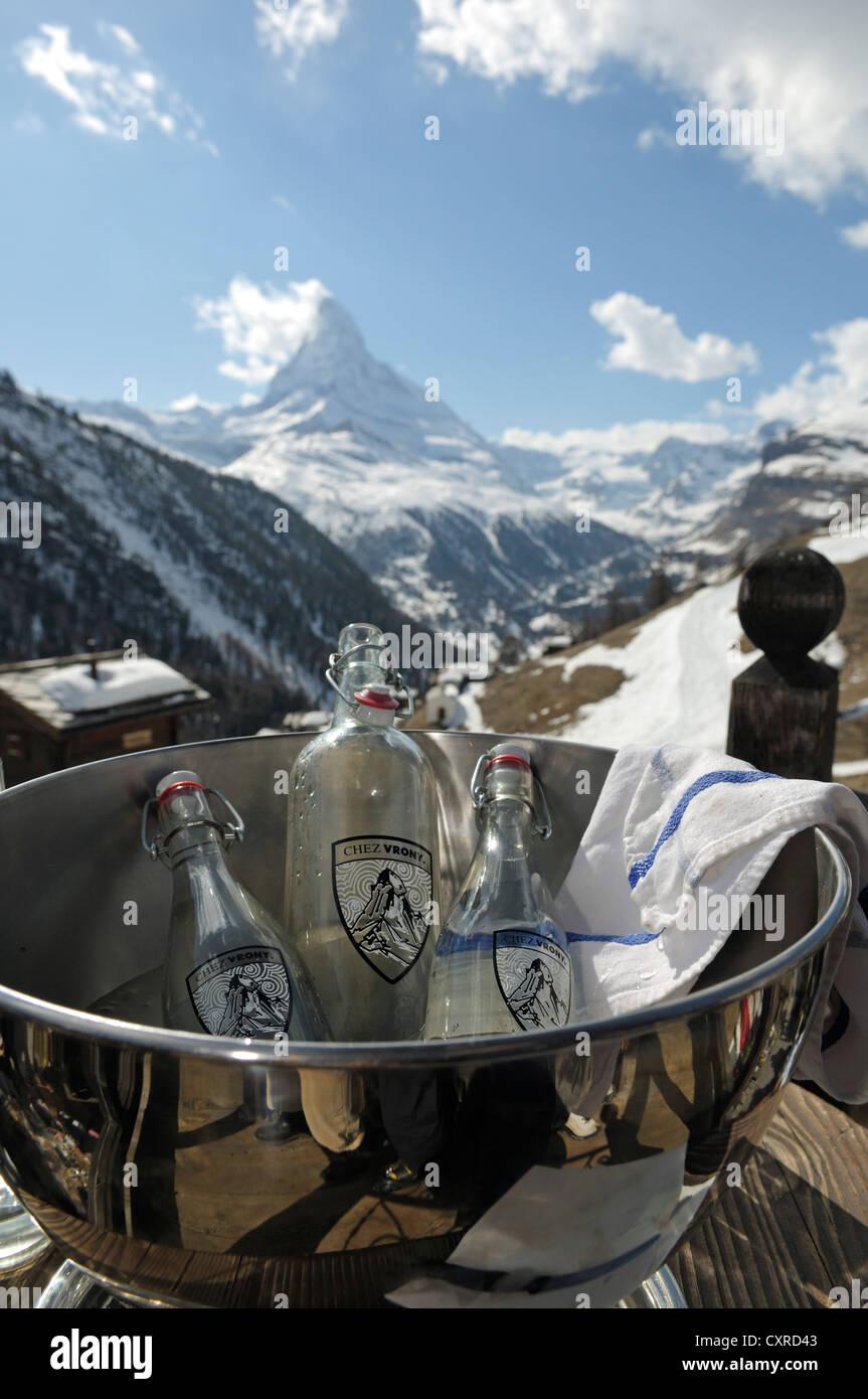 Mineral water in an ice bucket, Chalet Chez Vrony, restaurant, Mount Matterhorn at back, Zermatt, Valais, Switzerland, - Stock Image