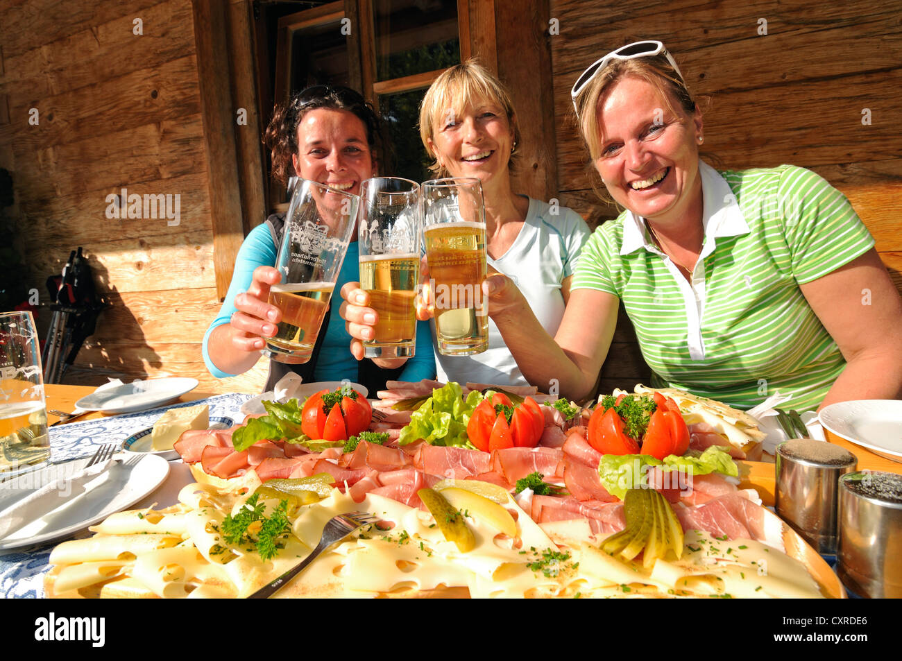 Women having a snack platter and beer after a hike Stock Photo