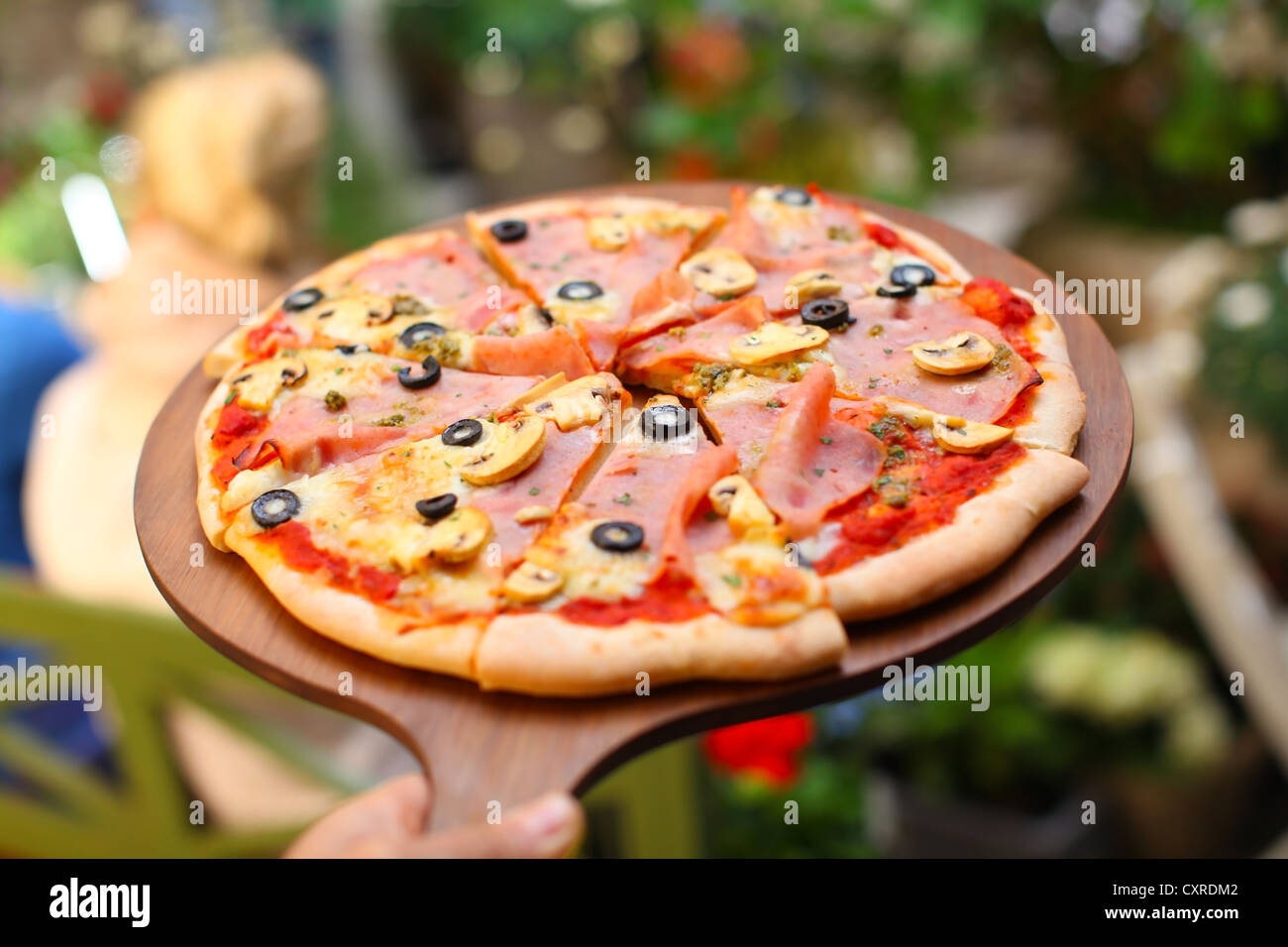 Whole pizza sliced in portions on pizza board - Stock Image