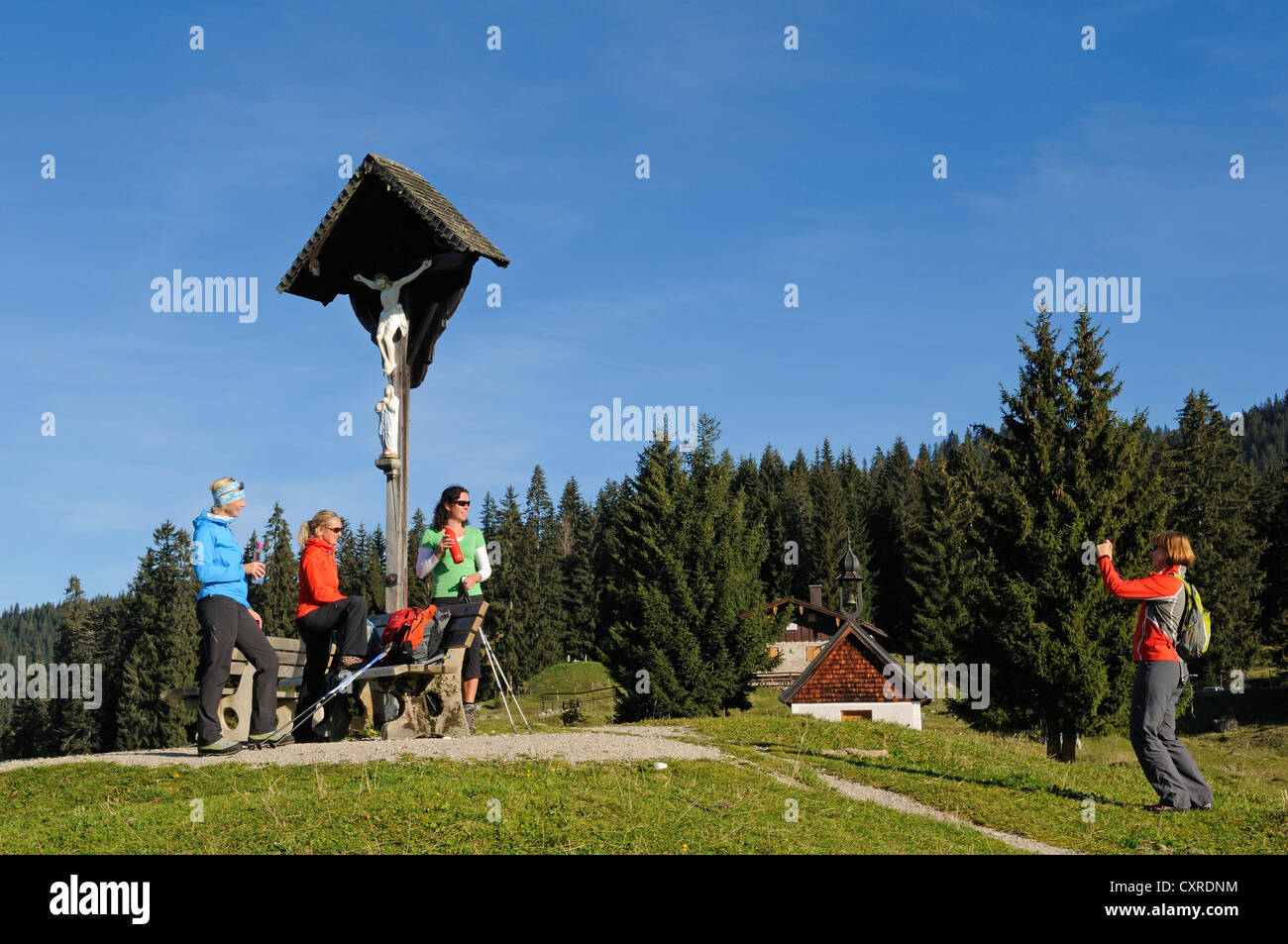 Female hikers having someone take a picture of them in front a cross on Winklmoosalm alp, Reit im Winkl, Chiemgau, - Stock Image