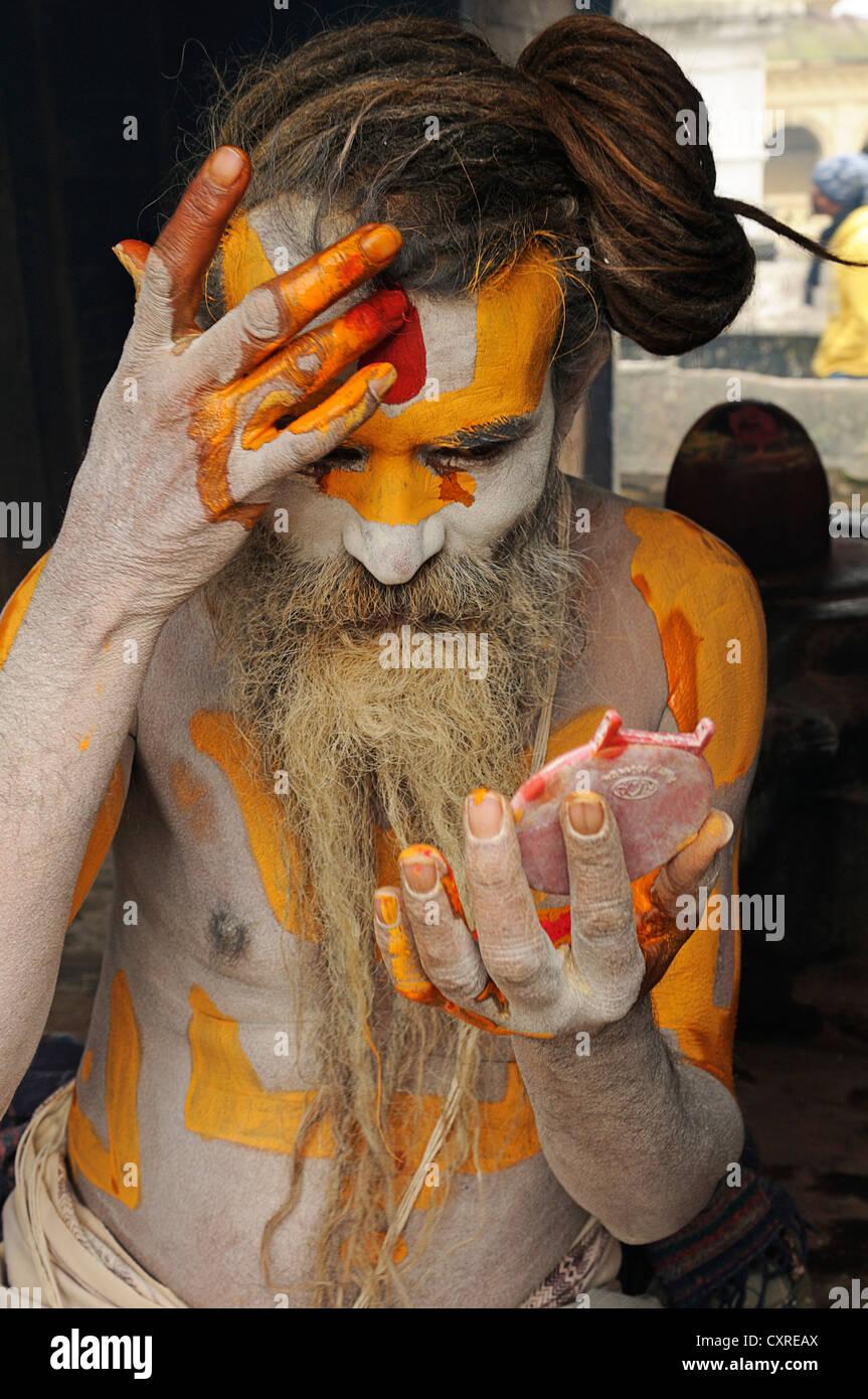Sadhu with dreadlocks painting himself, Pashupatinath, Kathmandu Valley, Nepal - Stock Image