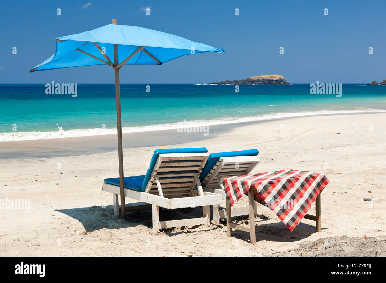 Sunloungers and a parasol at the beach, Pasir Putih or White Sand Beach, east of Candi Dasa, East Bali, Bali, Indonesia - Stock Image
