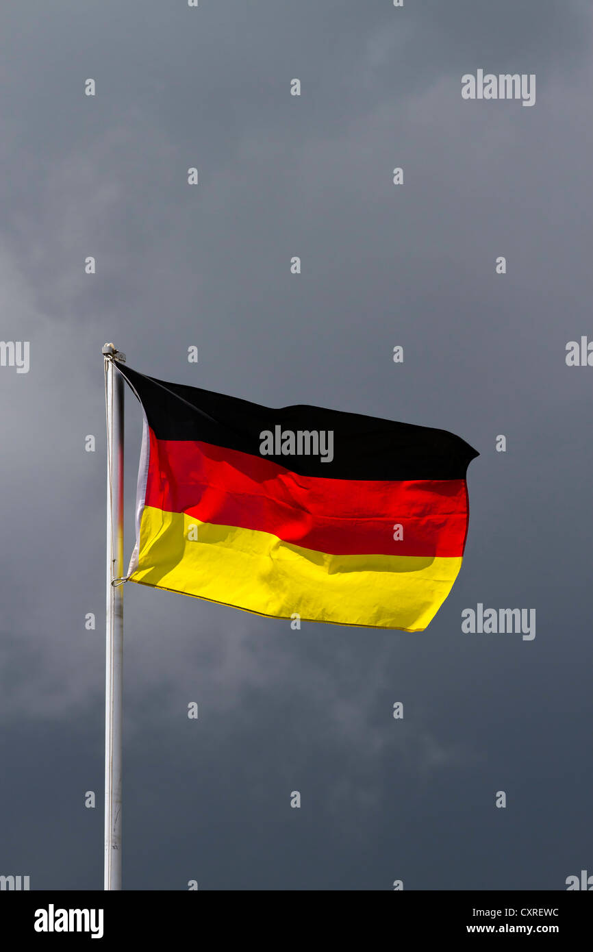The German national flag, dark clouds at the back, symbolic image - Stock Image