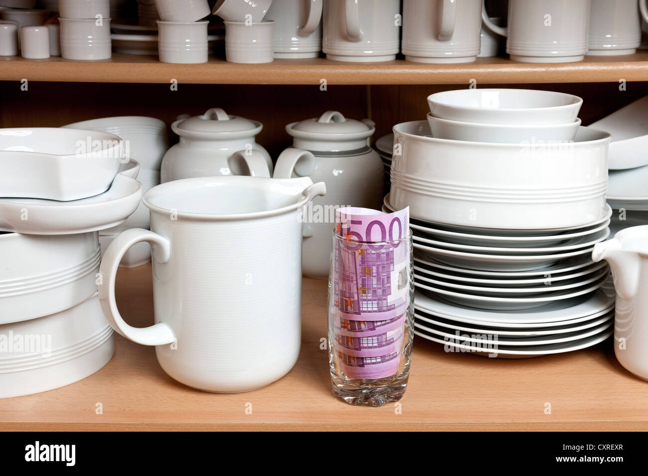 Money in the kitchen cupboard, between cups and plates - Stock Image