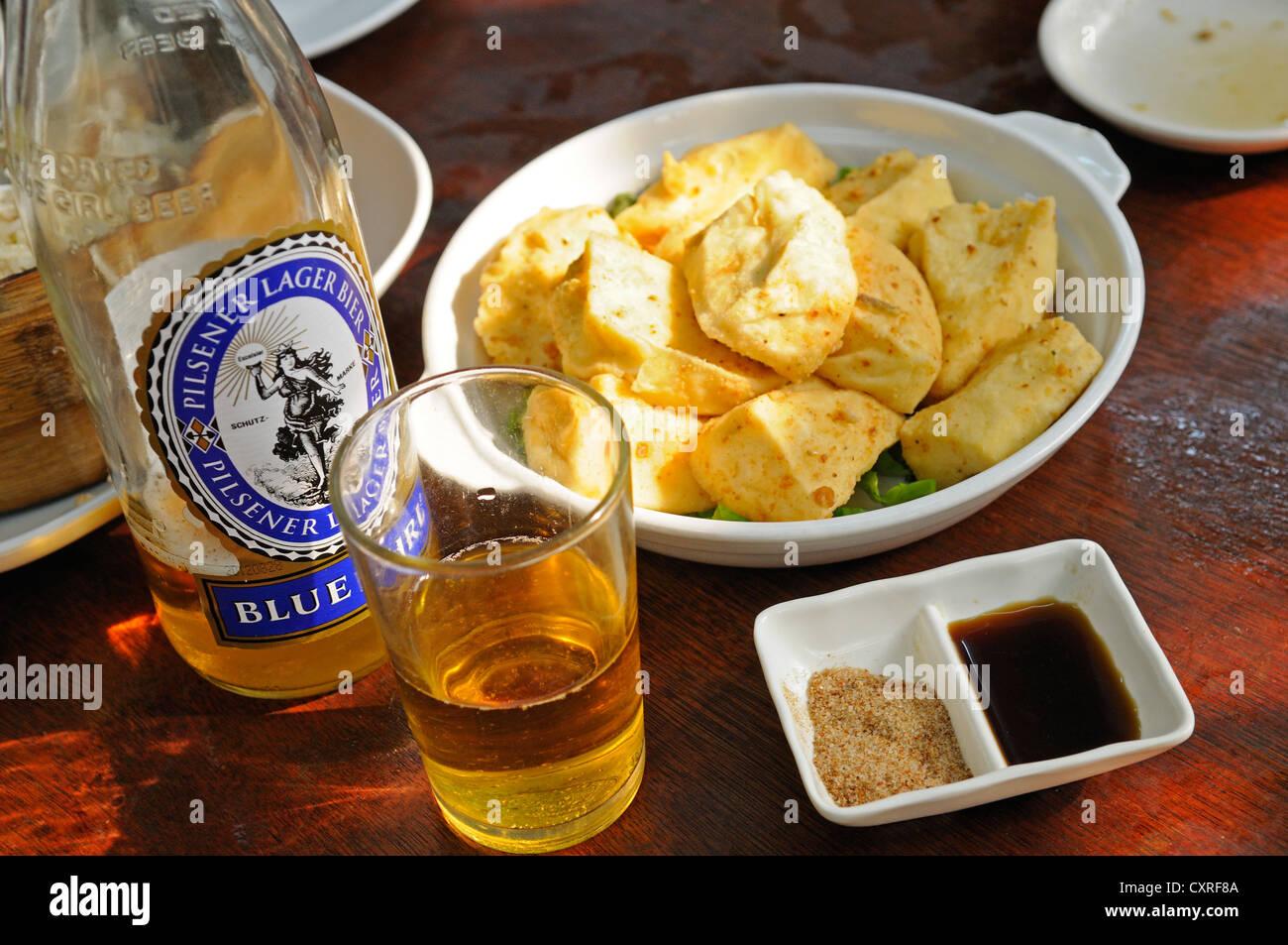 Blue Girl beer with fish at the restaurant of the Tai O Fishing Village, Lantau Island, Hong Kong, China, Asia - Stock Image