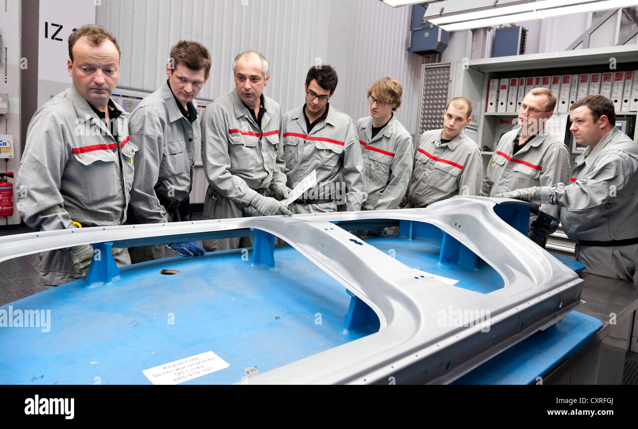 A foreman showing employees a body panel instructing them for the upcoming mould change at the pressing plant, AUDI - Stock Image