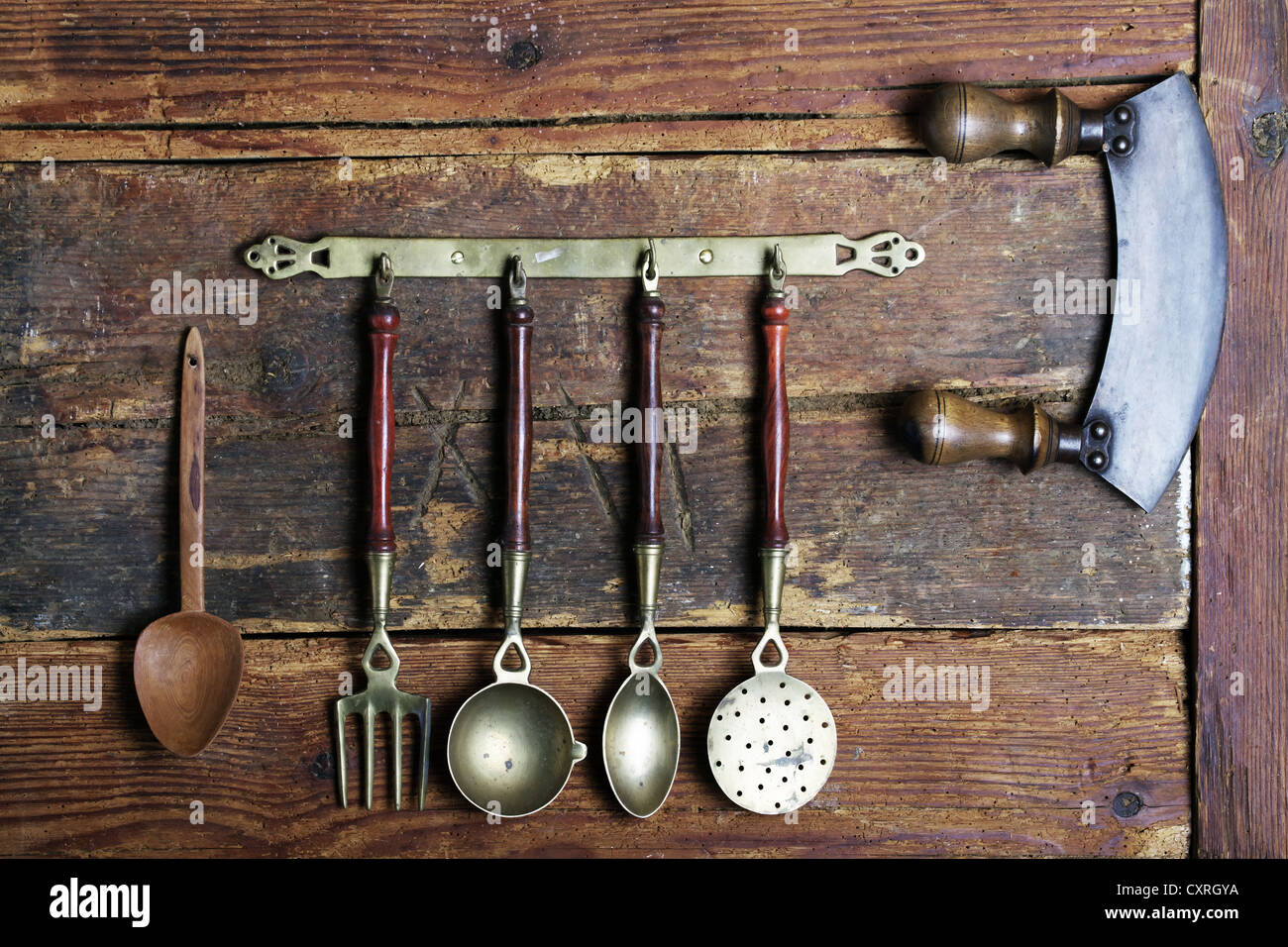 Old Kitchen Utensils Made Of Brass Hanging From A Bar In Front Of A Rustic  Wooden