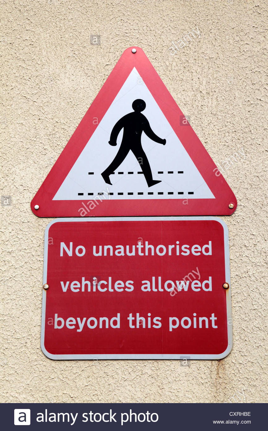 A red & white triangular pedestrian crossing point sign and a No unauthorised vehicles allowed beyond this point - Stock Image