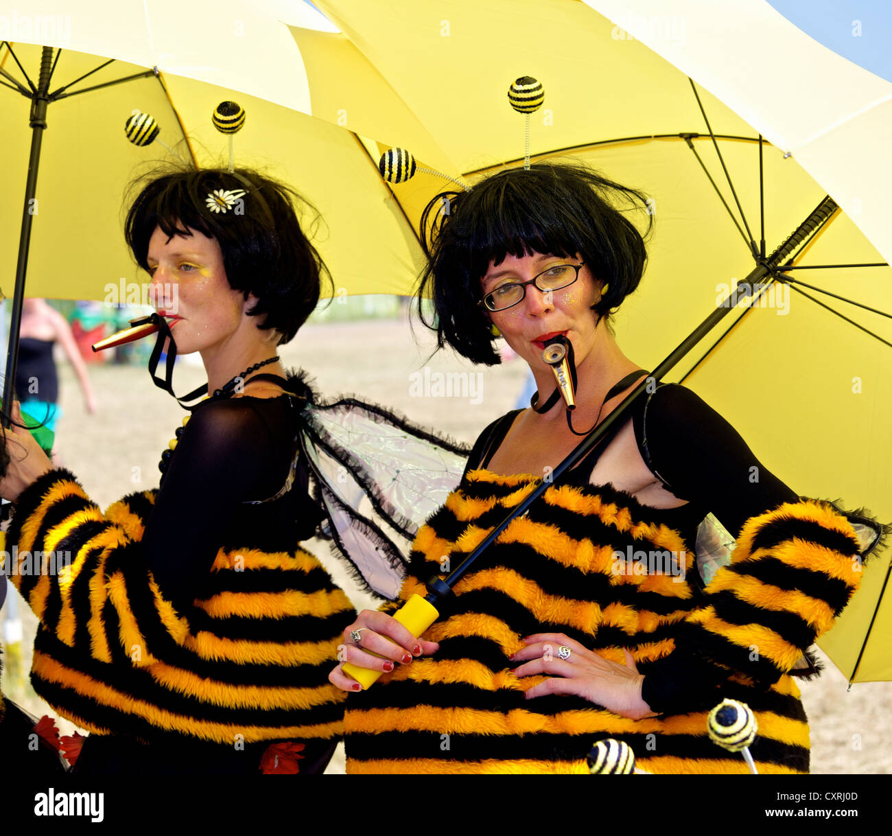 Two women  playing Kazoos whilst sheltering from the sun under a large yellow umbrella at the Glastonbury Festival - Stock Image