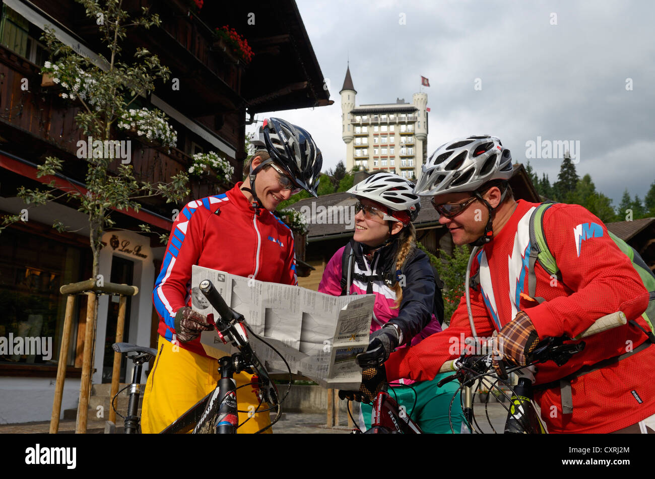 Mountain bikers with a map outside the Palace Hotel Gstaad Stock