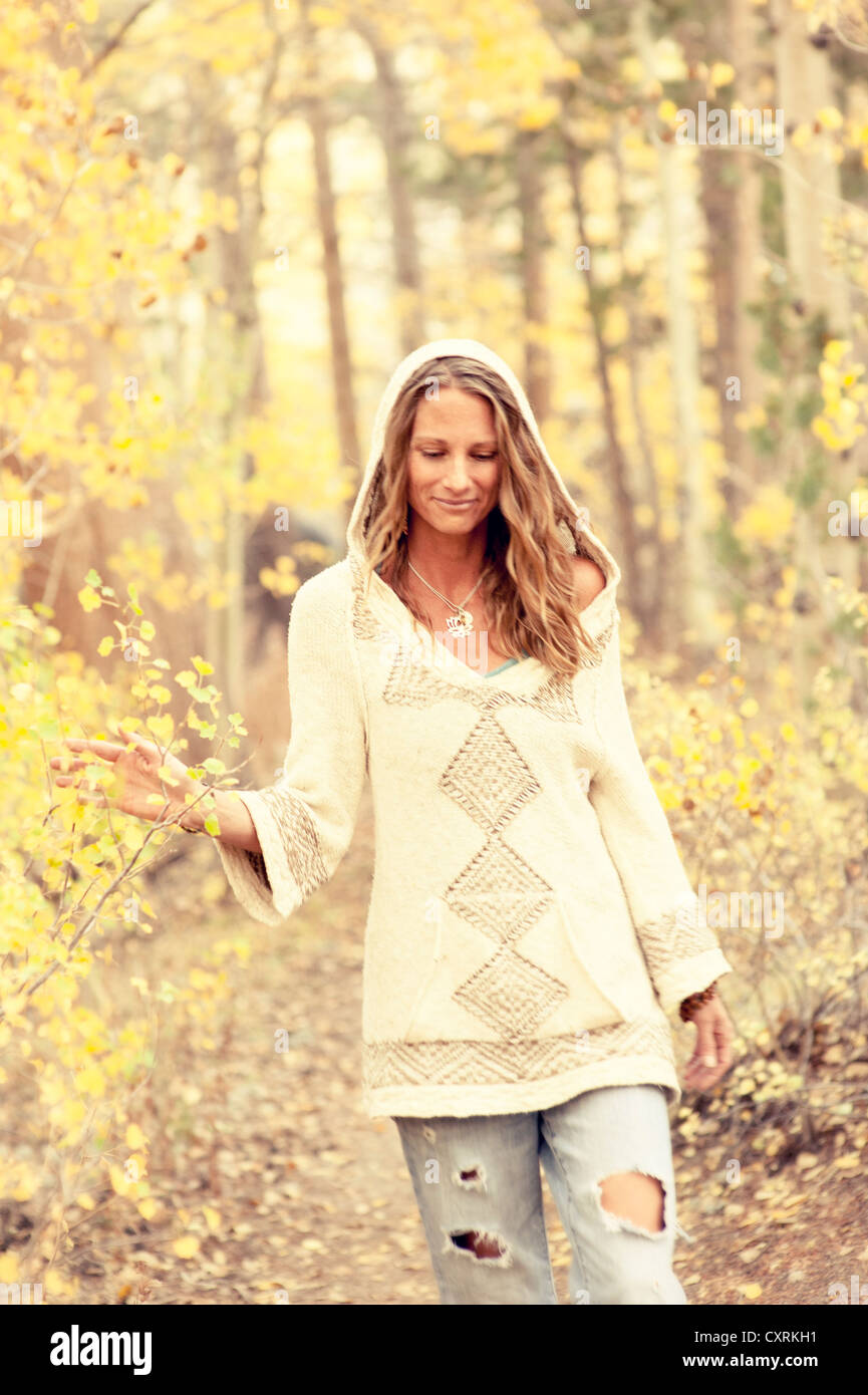 Natural casual woman in a jeans and sweater walking through the yellow autumn leaves. - Stock Image