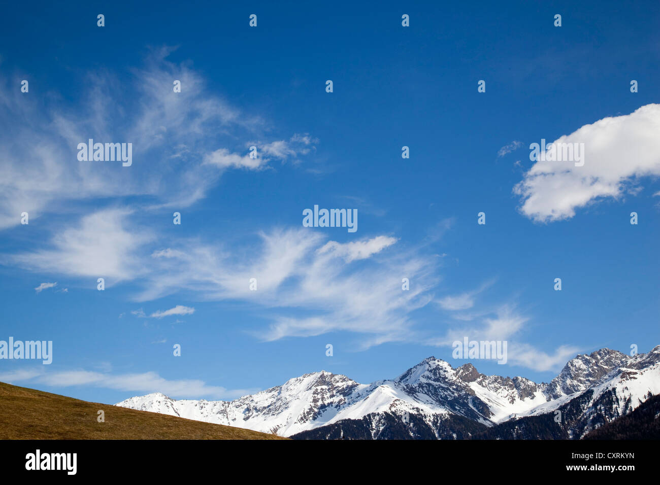 Colour landscape of  of Alpine Mountains, and a blue wispy clouded sky. - Stock Image
