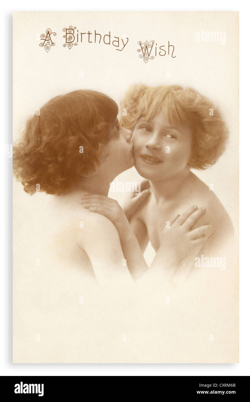 Birthday greetings photograph, sent in 1931, featuring two young girls, one giving the other a birthday kiss. - Stock Image