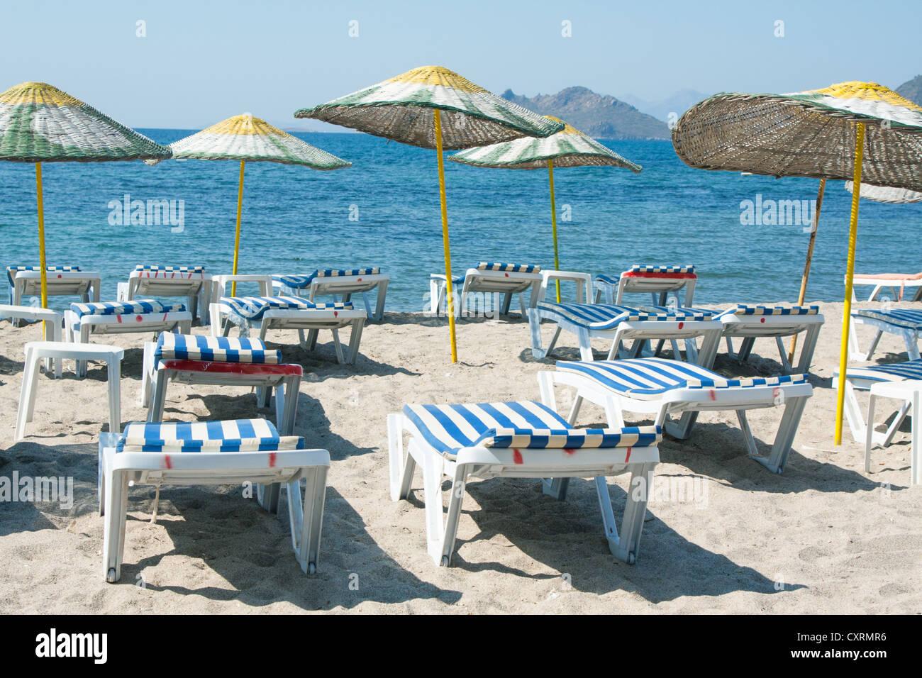 Sun loungers and wicker umbrellas on sandy beach Stock Photo