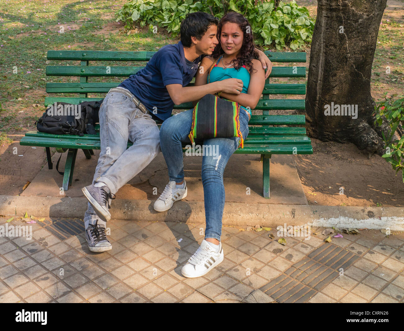 Two Teenage Lovers Embrace On A Park Bench In A City Park In Stock