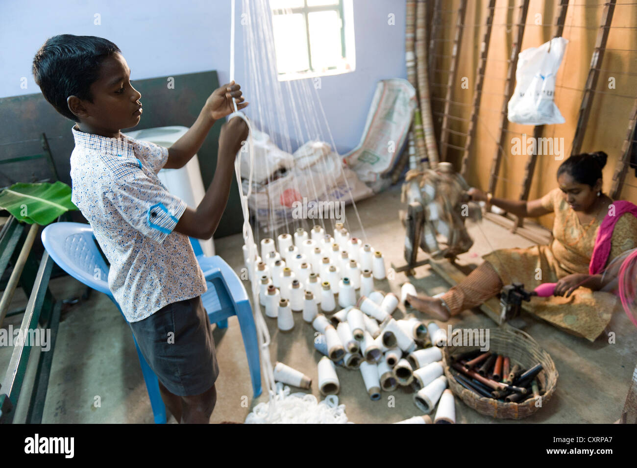 Child labourers working in a mosquito net factory, Karur, Tamil Nadu, South India, India, Asia - Stock Image
