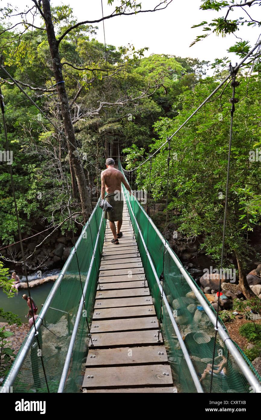 Tourist walking on the suspension bridge leading to the hot springs, near the Hacienda Guachipelin, near Liberia - Stock Image