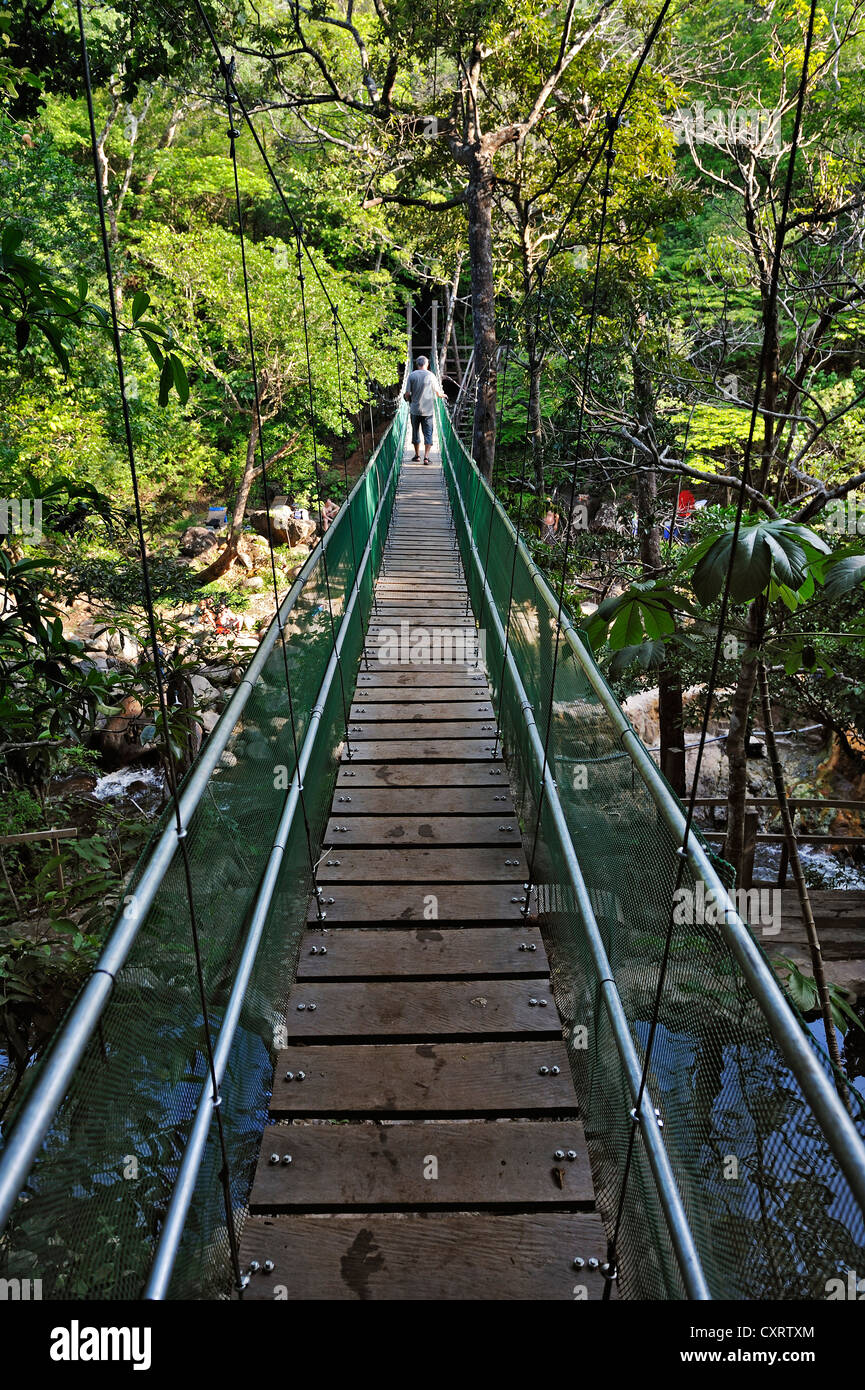 Suspension bridge leading to the hot springs near the Hacienda Guachipelin, near Liberia, Guanacaste province, Costa - Stock Image