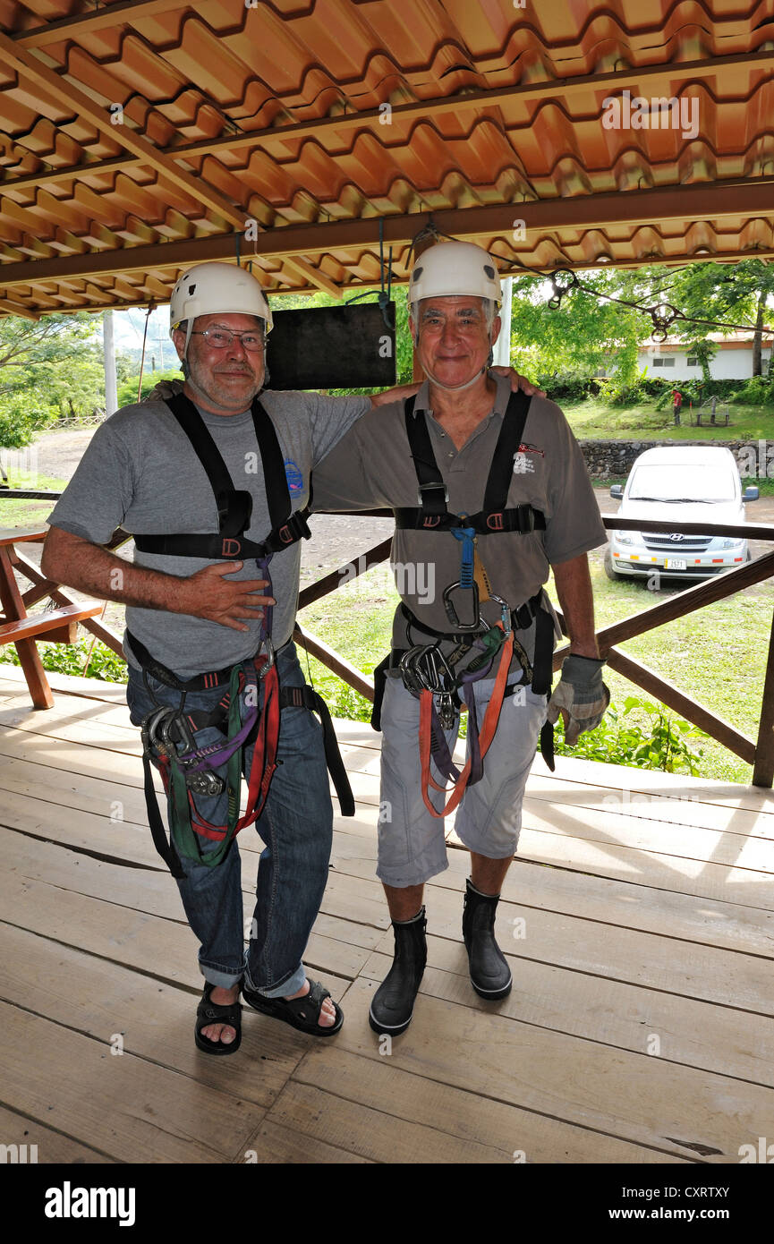 Two tourists, senior citizens, equipped for a canopy rope tour on the Hacienda Guachipelin near Liberia, Guanacaste - Stock Image