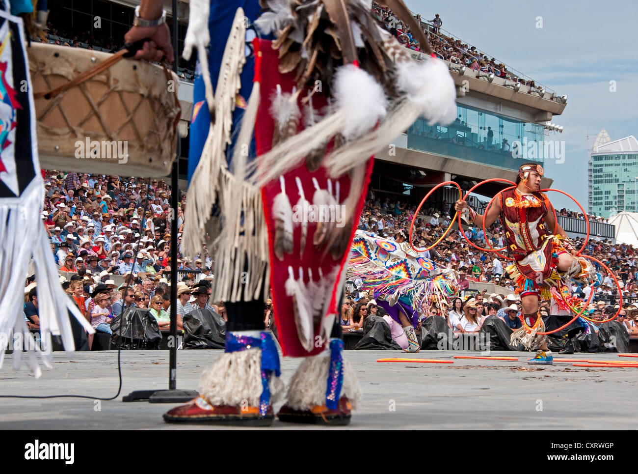 First Nations hoop dancer accompanied by drummers at the Calgary Stampede 2012. - Stock Image