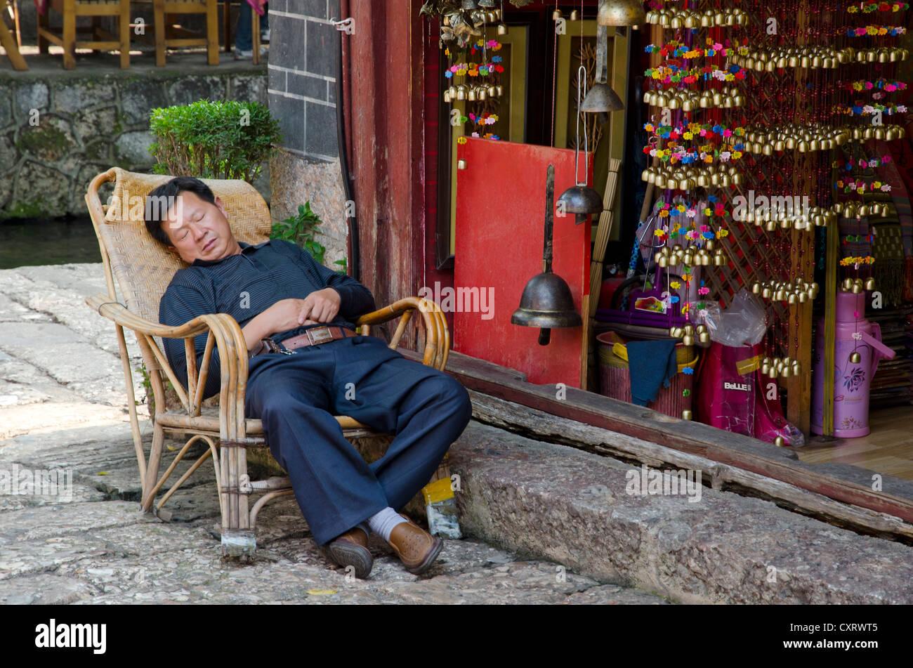 Shopkeeper asleep in front of his shop, Lijiang, Yunnan, southeast China, China, Asia - Stock Image