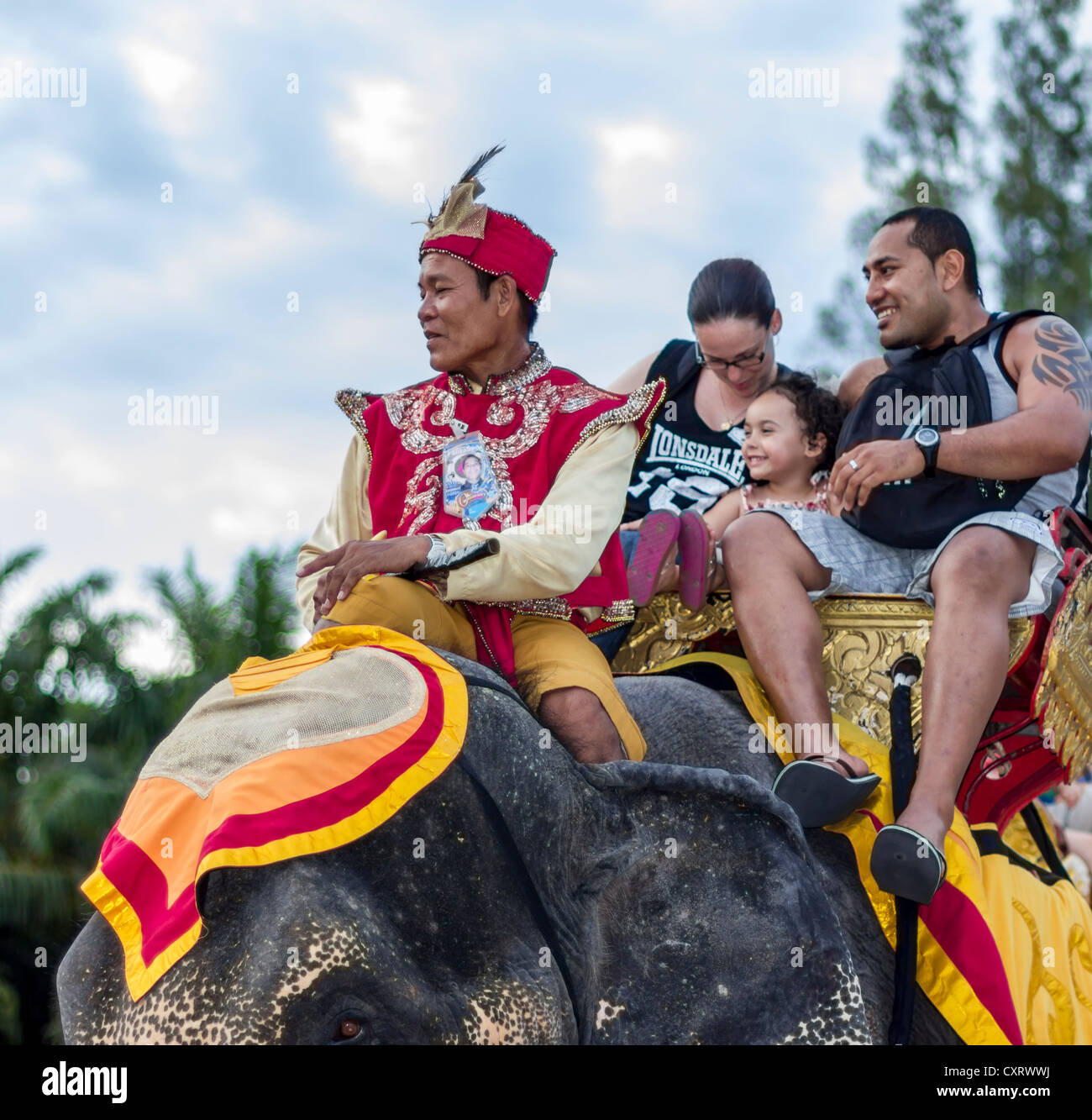 Family on elephant ride at Fantasea amusement park, Phuket, Thailand. - Stock Image
