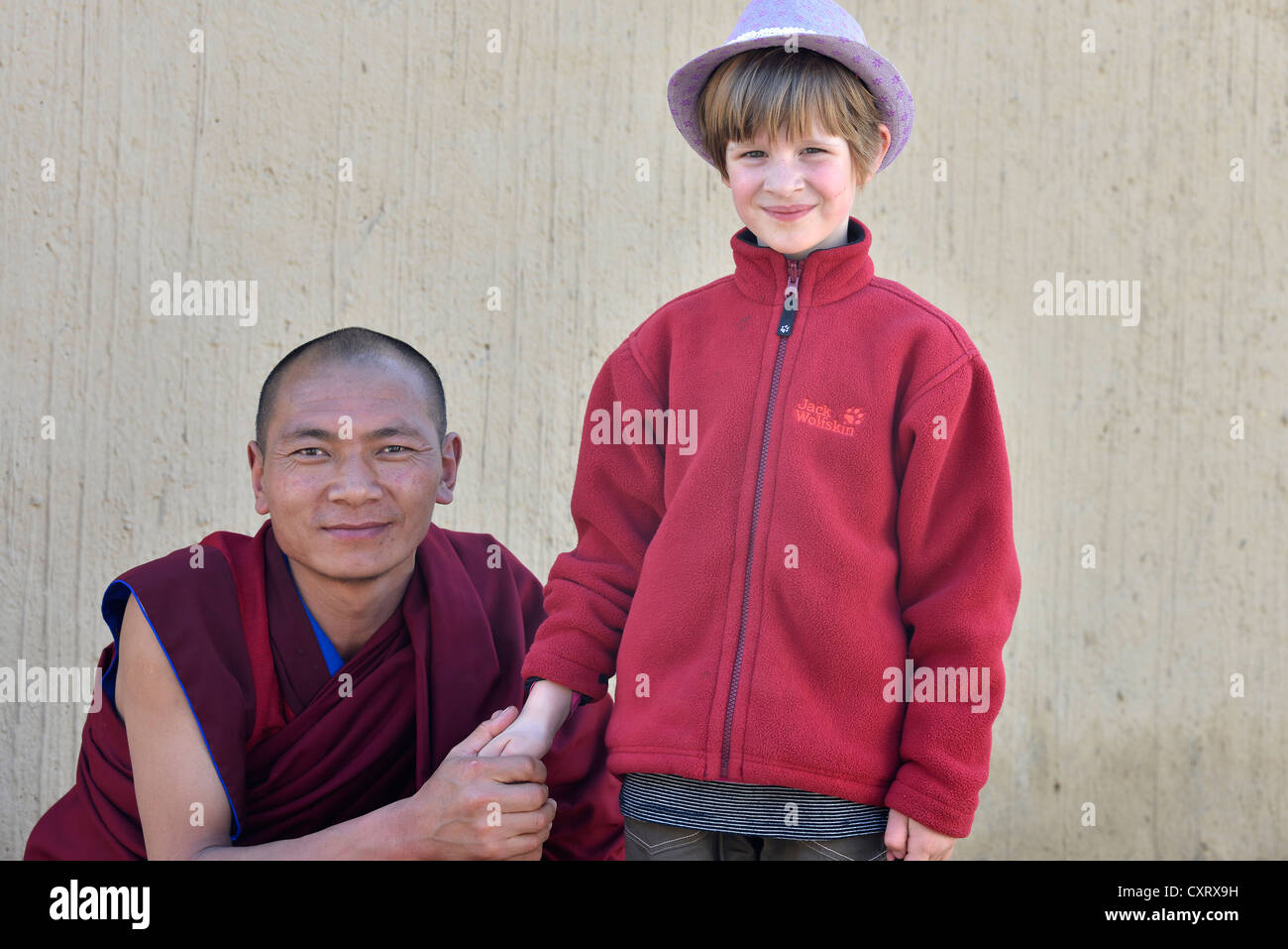 Monk holding the hand of a European child, 6 years, Labrang Monastery, Xiahe, Gansu, formerly Amdo, Tibet, China, - Stock Image