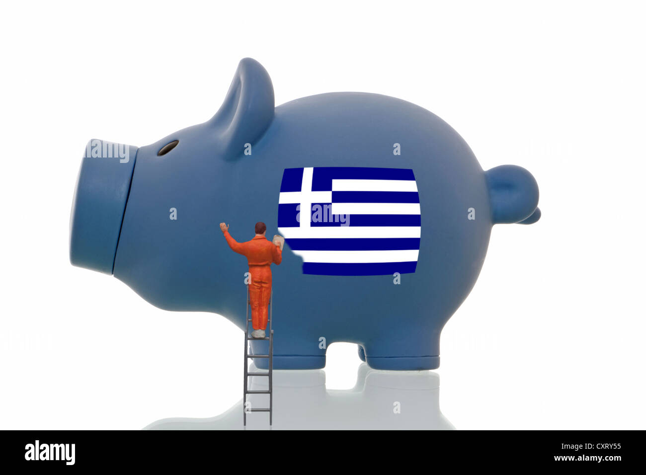Miniature figurine painting over a Greek national flag on a blue piggy bank, symbolic image - Stock Image