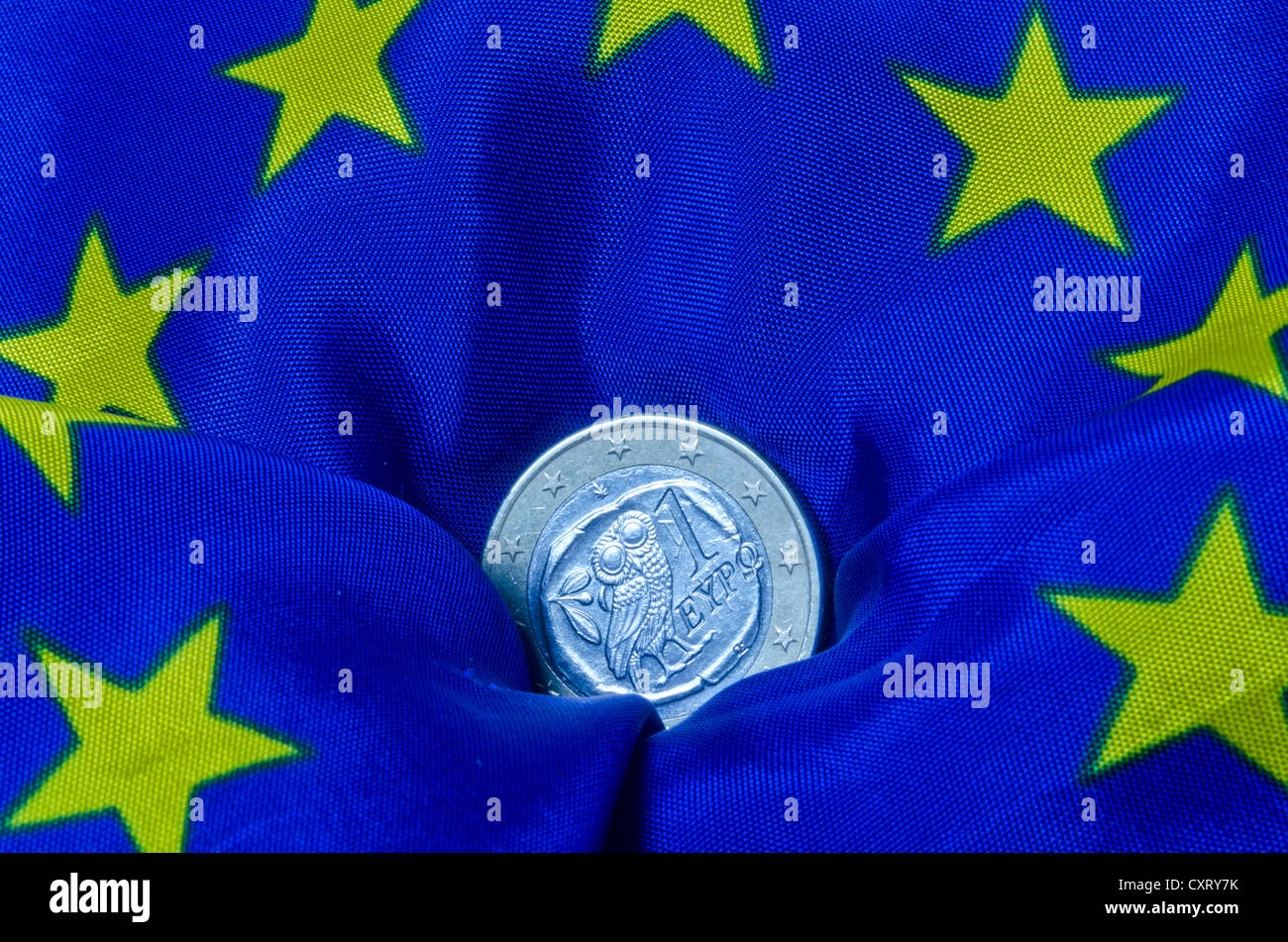Greek euro coin lying on an European flag, going down, symbolic image - Stock Image