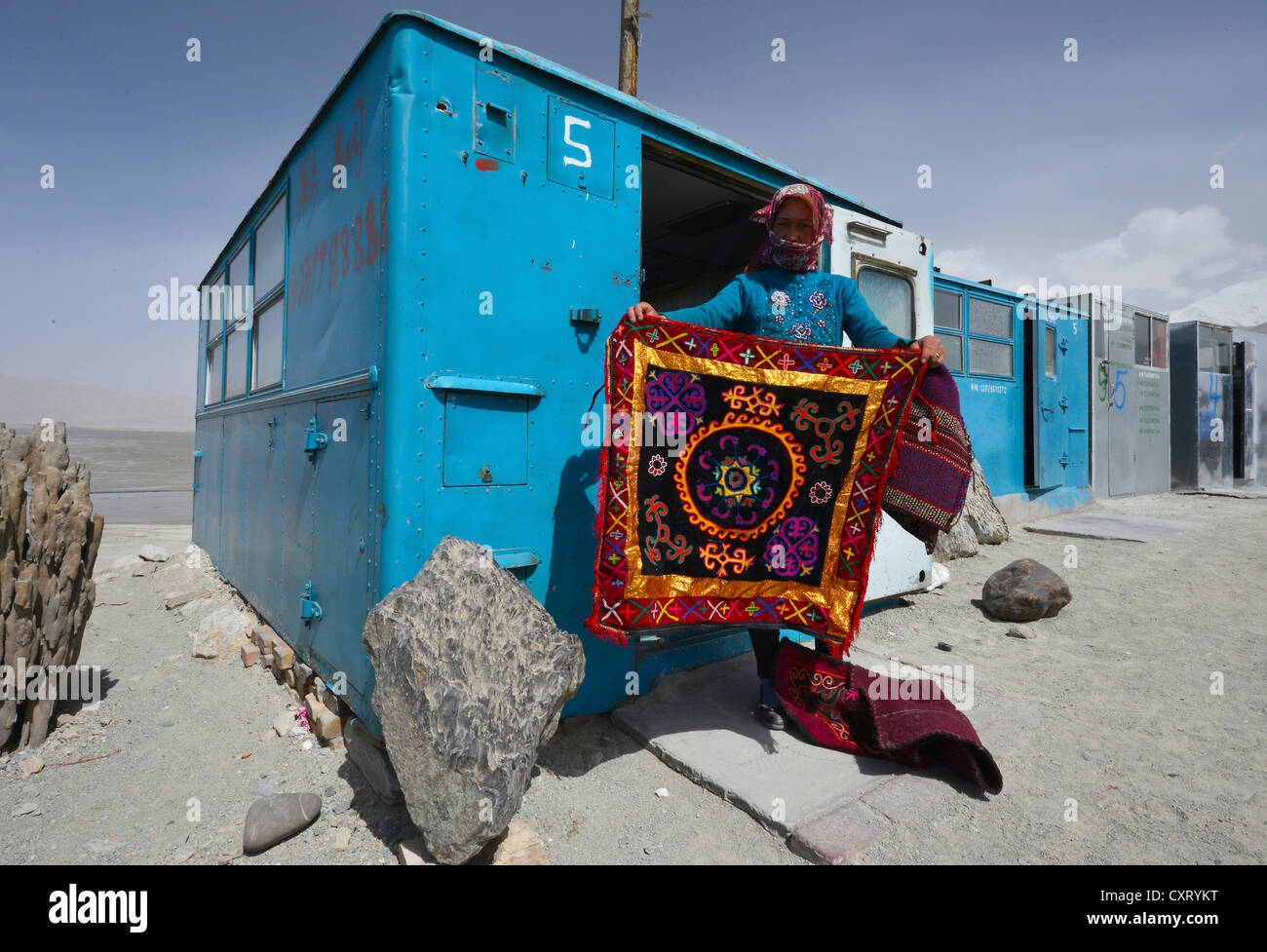 Kazakh woman showing a hand-woven, embroidered wall carpet, simple blue containers, house boxes, storage containers, - Stock Image