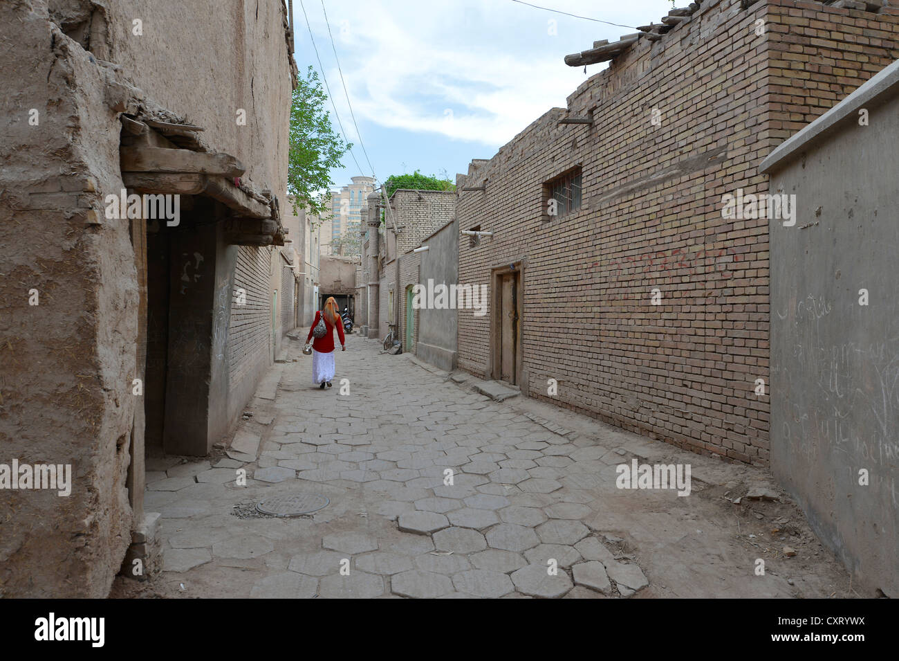 Muslim woman walking though an alleyway in the old town of the Uyghur quarter, old adobe brick architecture, Silk Stock Photo