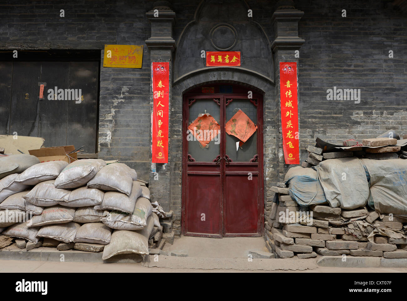 Cement sacks in front of an old Chinese house in the historical old town of Pingyao, UNESCO World Heritage Site, - Stock Image