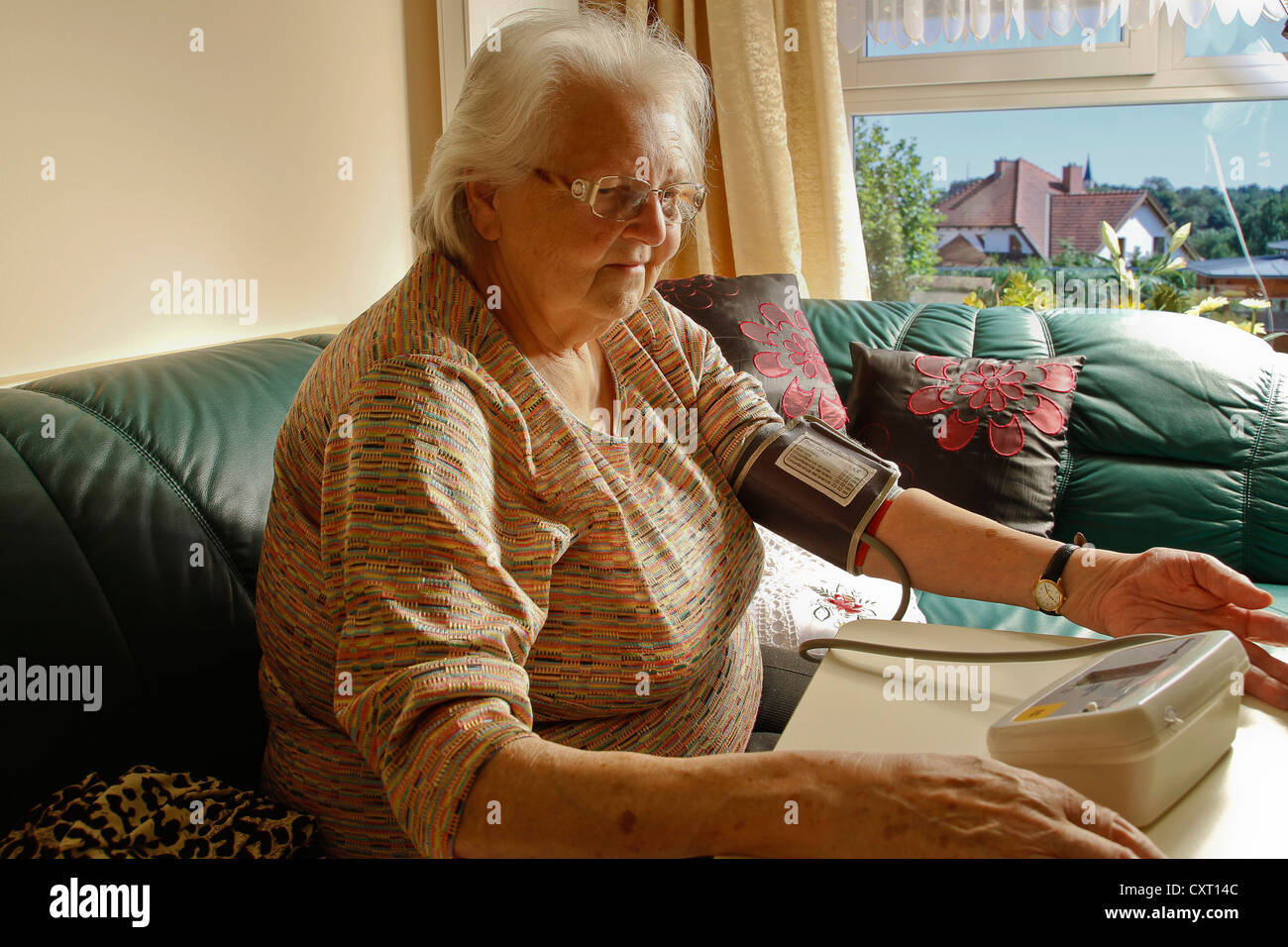 Old woman with a blood pressure gauge - Stock Image
