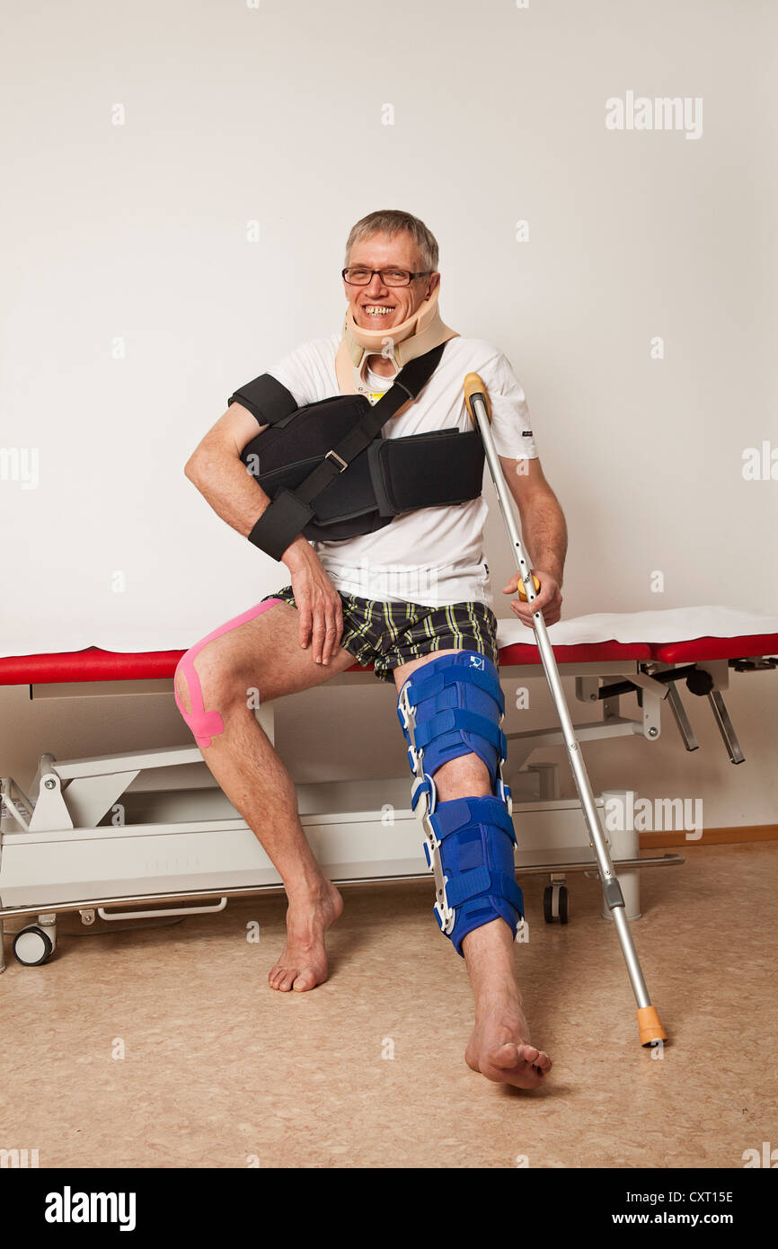 Man with kinesio taping wearing a shoulder abduction pad, a foot orthosis and a cervical support - Stock Image