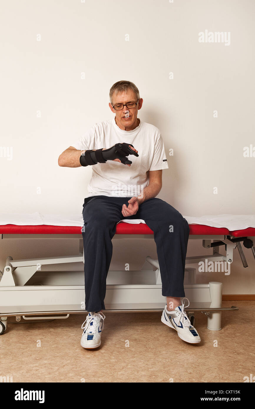 Man wearing a hand orthosis - Stock Image